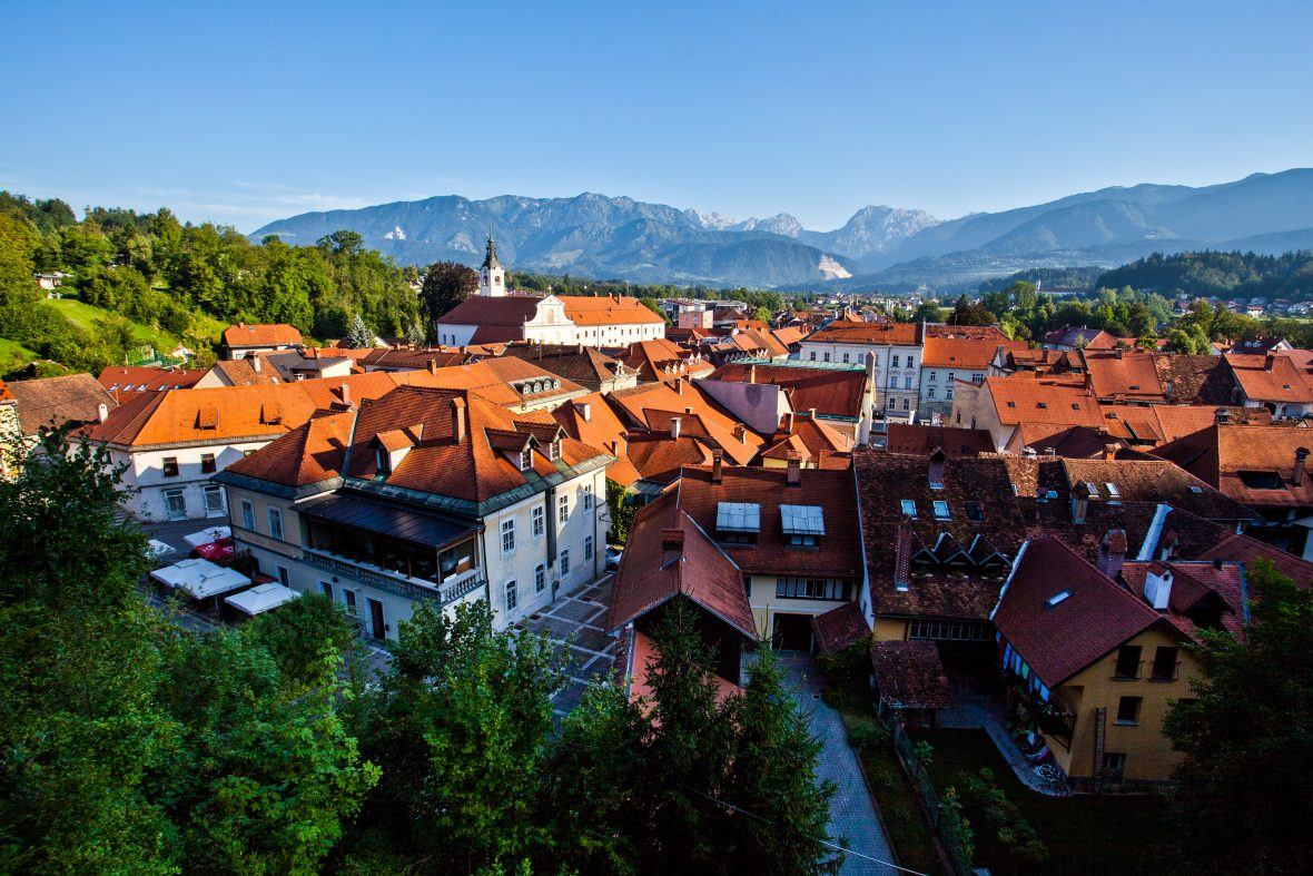 Aerial view of the town of Kamnik, Slovenia features pedestrianized sections, rows of uninterrupted, 18th century burger homes, red slate tile roofs, church towers, and utter late Baroque loveliness.