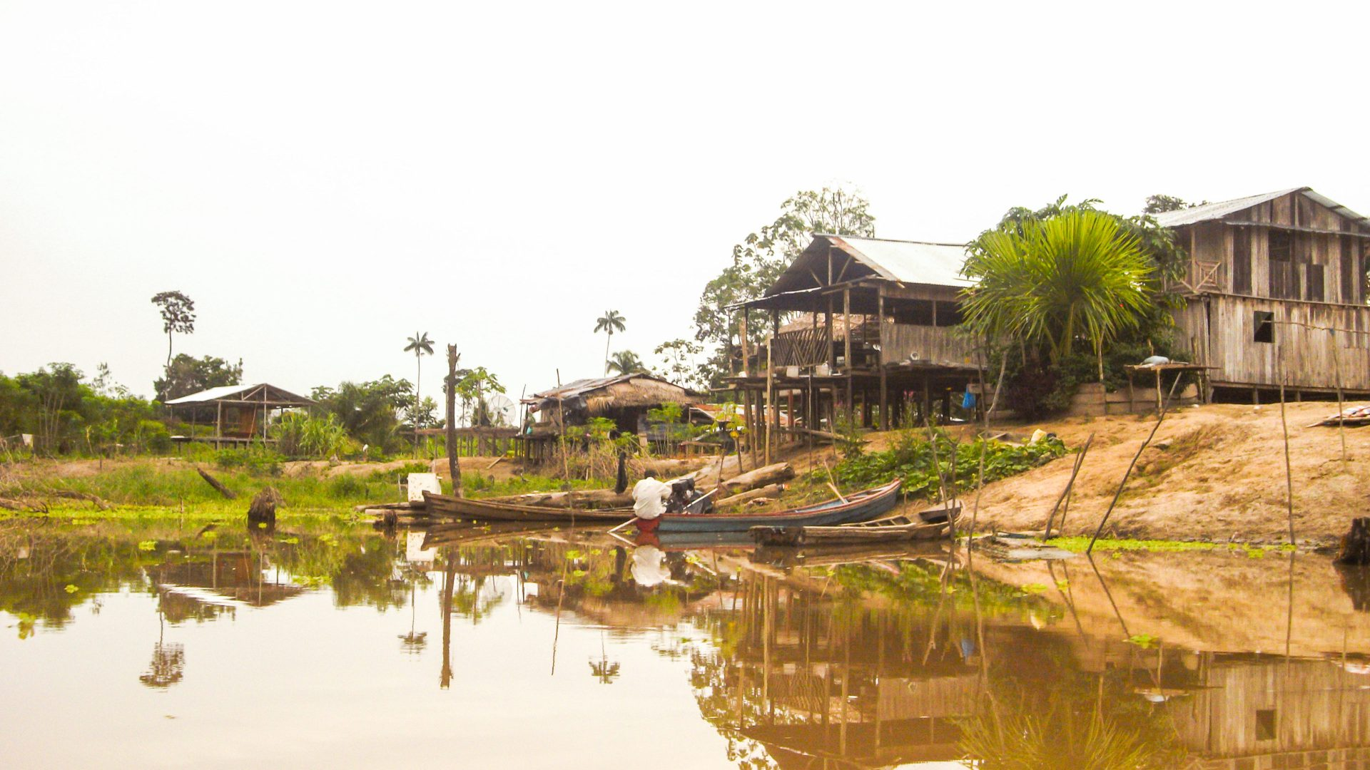 A man on a small canoe can be seen in the river in front of a house in the Amazon jungle.