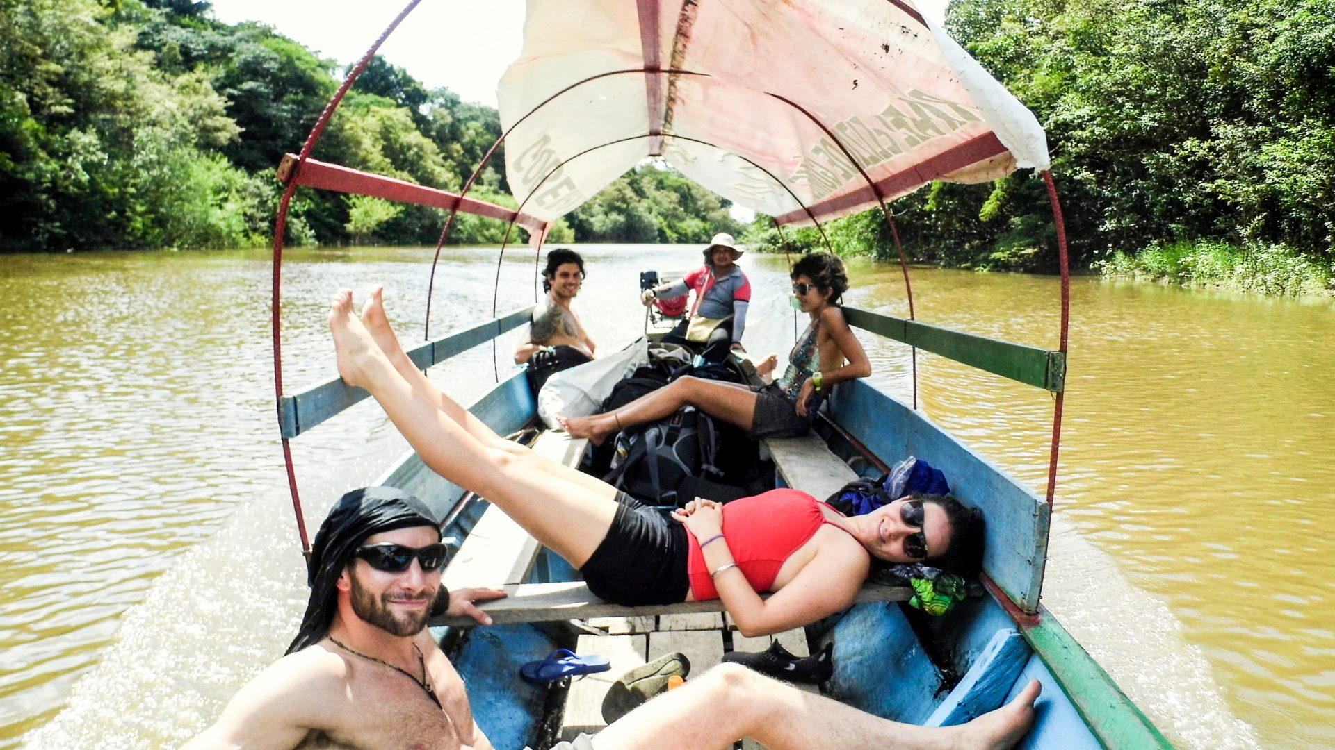 Tourists recline in the sunshine as their boat moves through the river in the Amazon jungle.