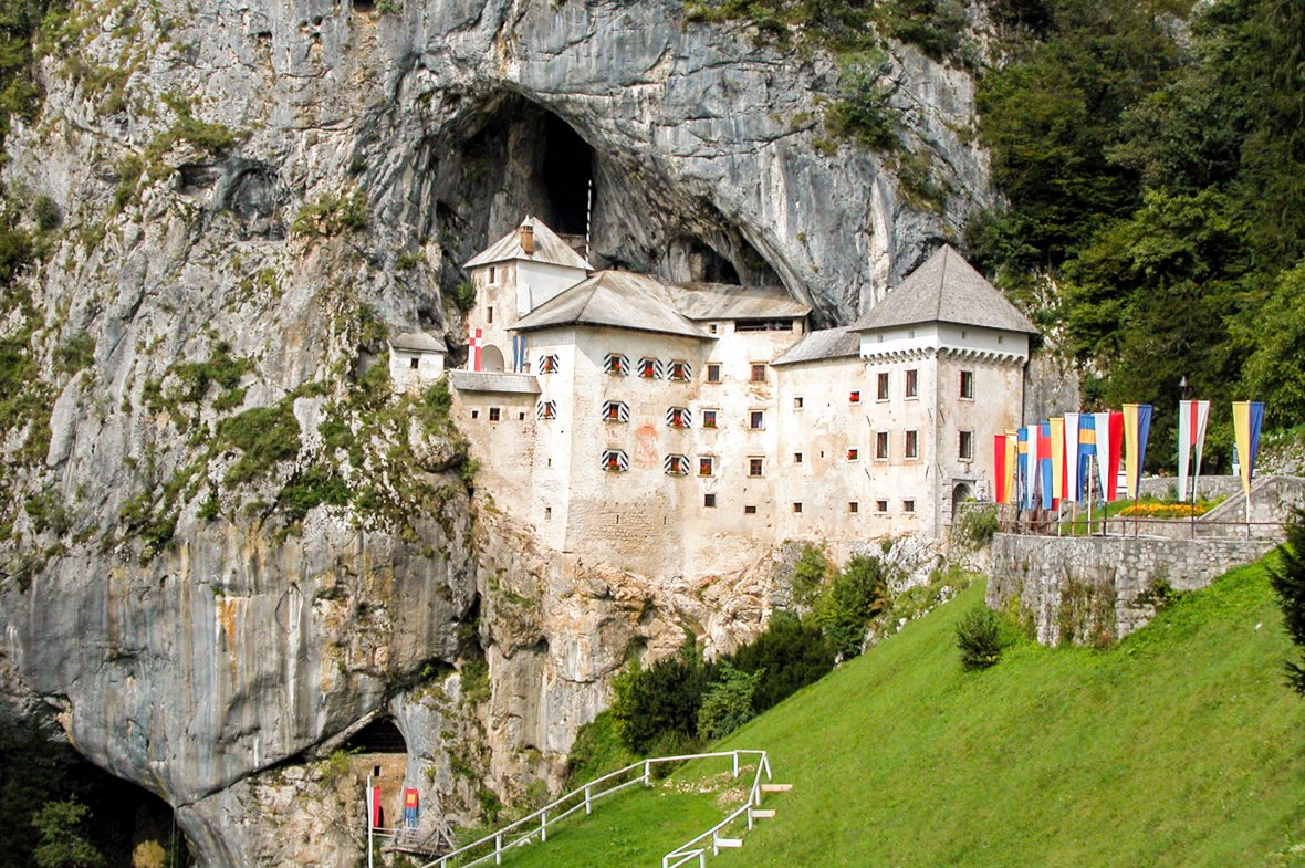 Predjamski Grad, Slovenia which is a castle carved into a sheer cliff face.