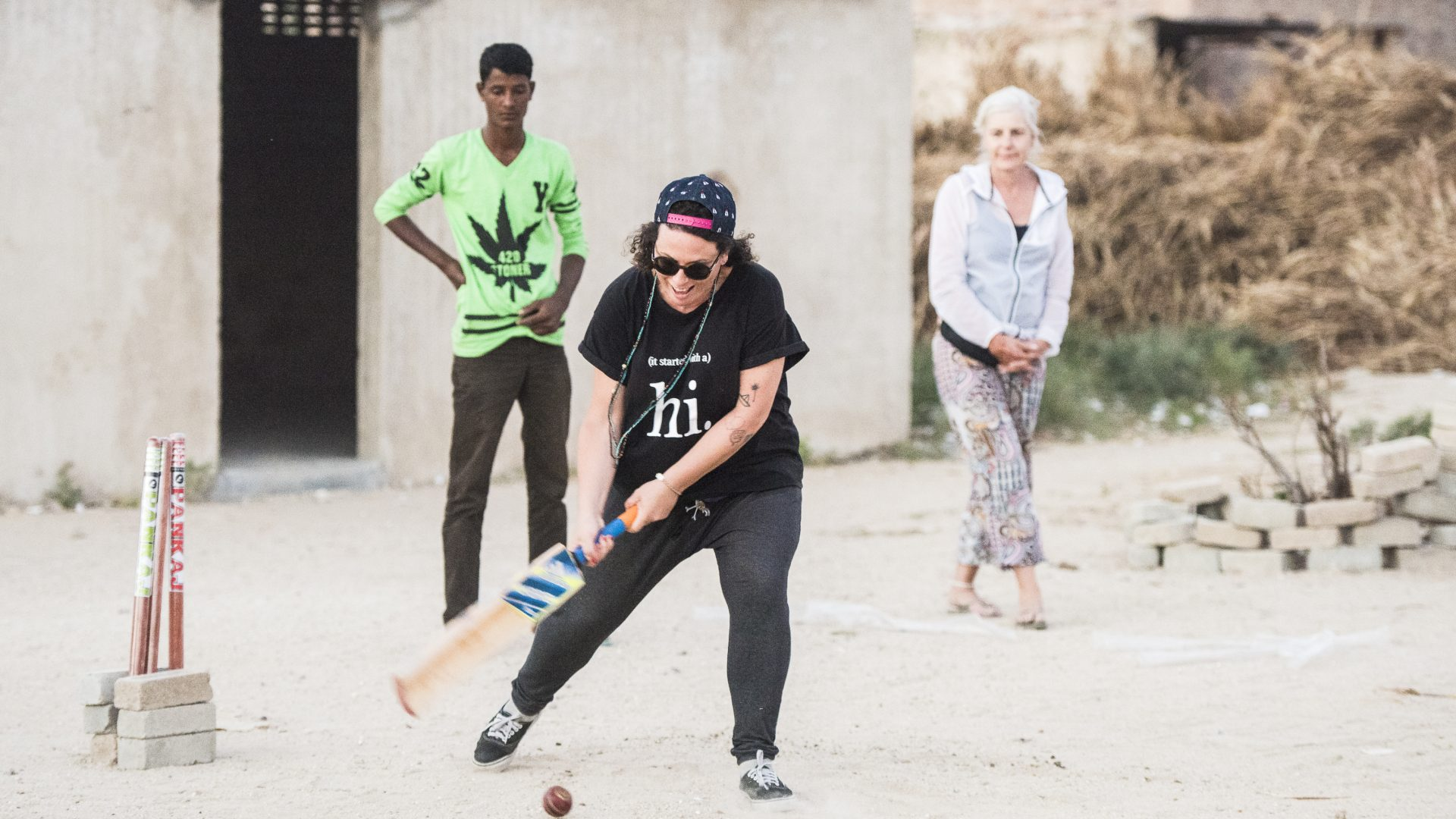 A tourist plays cricket with some locals in India