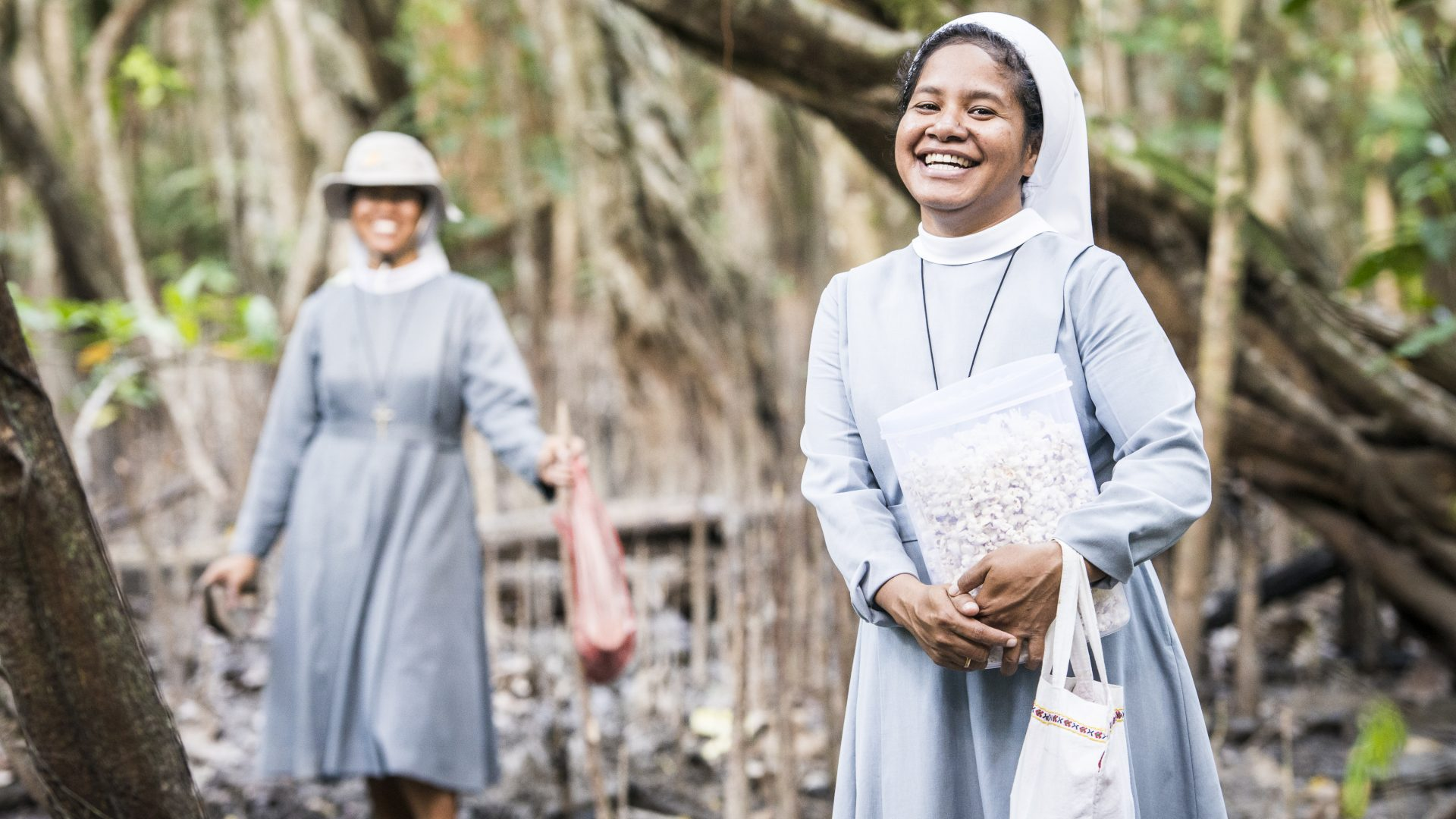 Nuns from East Timor have a laugh while standing in a swamp, carrying popcorn.