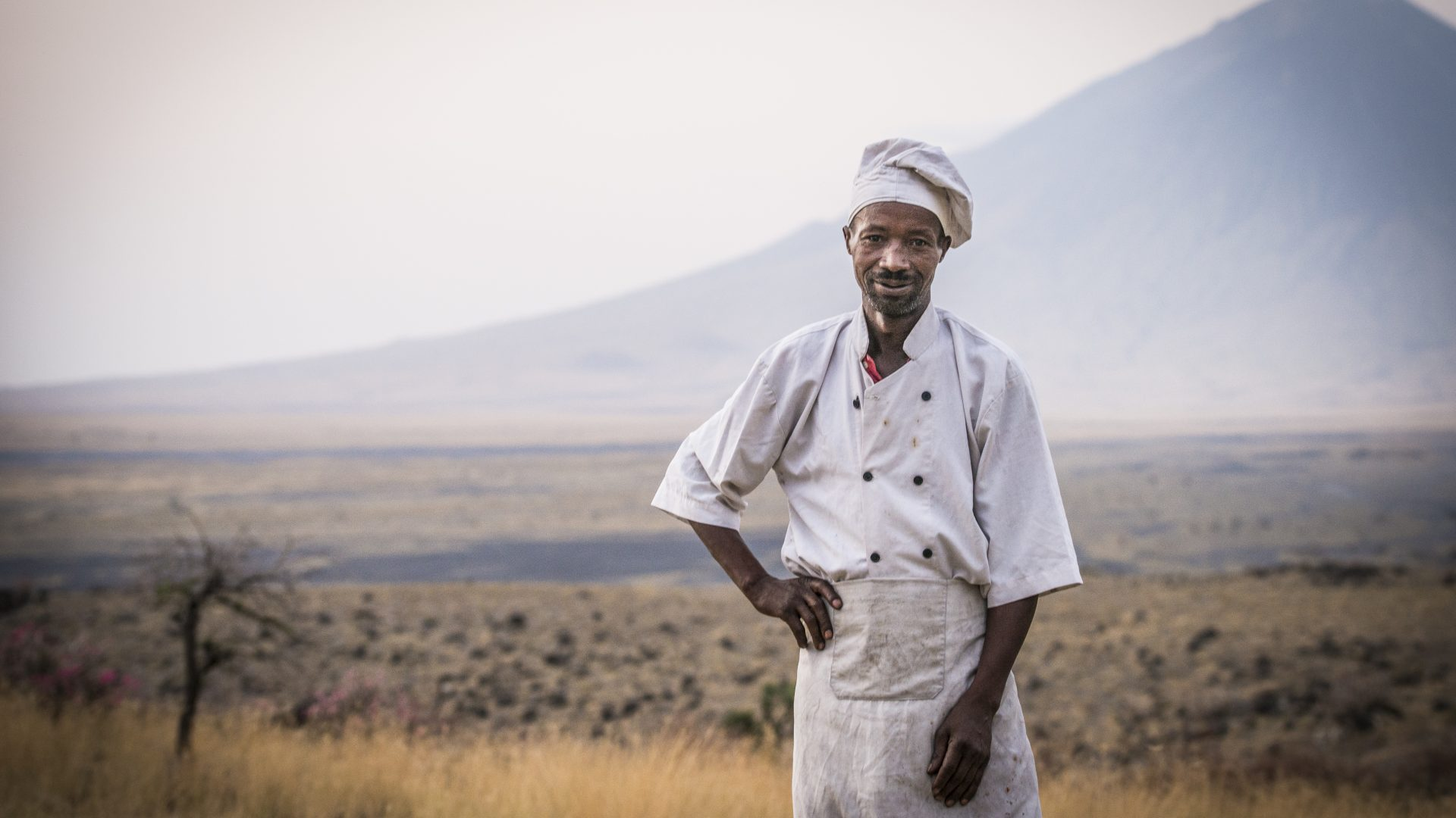 A chef, working at dawn at a campsite at Lake Natron, Tanzania, pauses for his portrait.