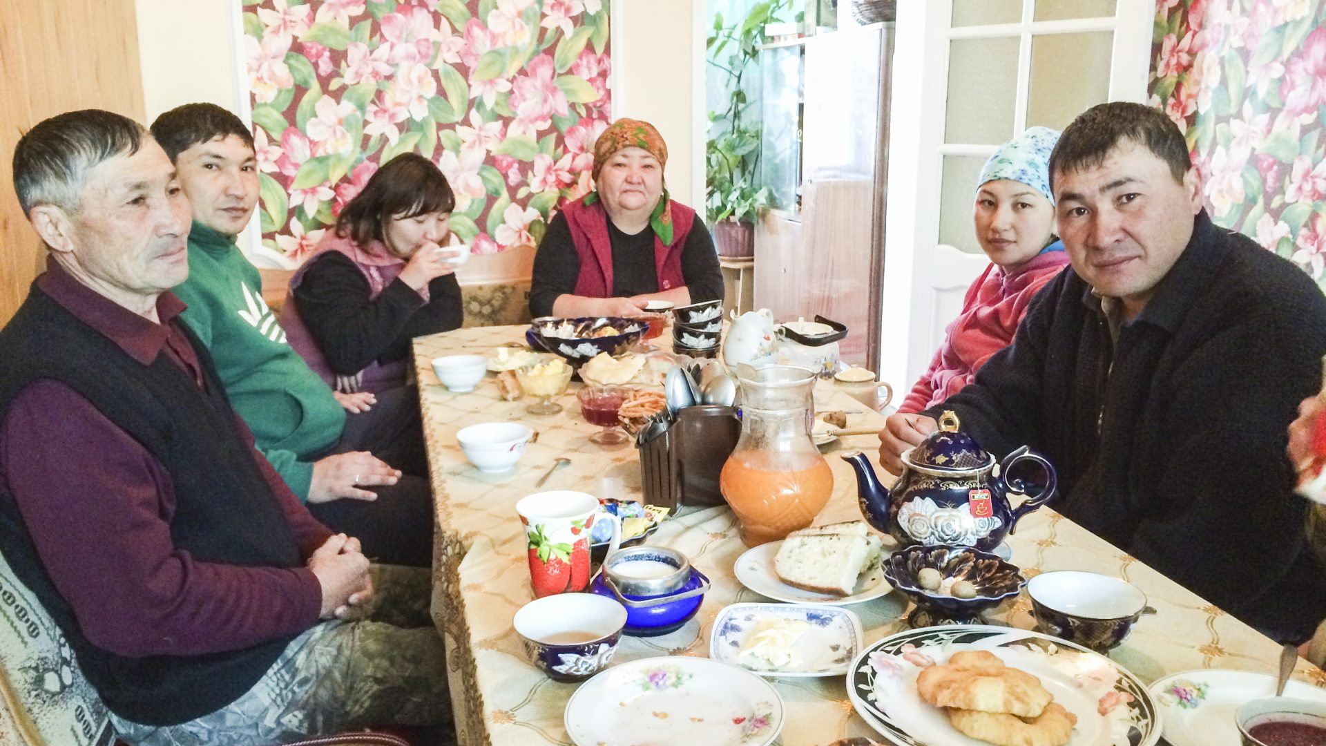 Group of people sits around a table of food in Kyrgyzstan