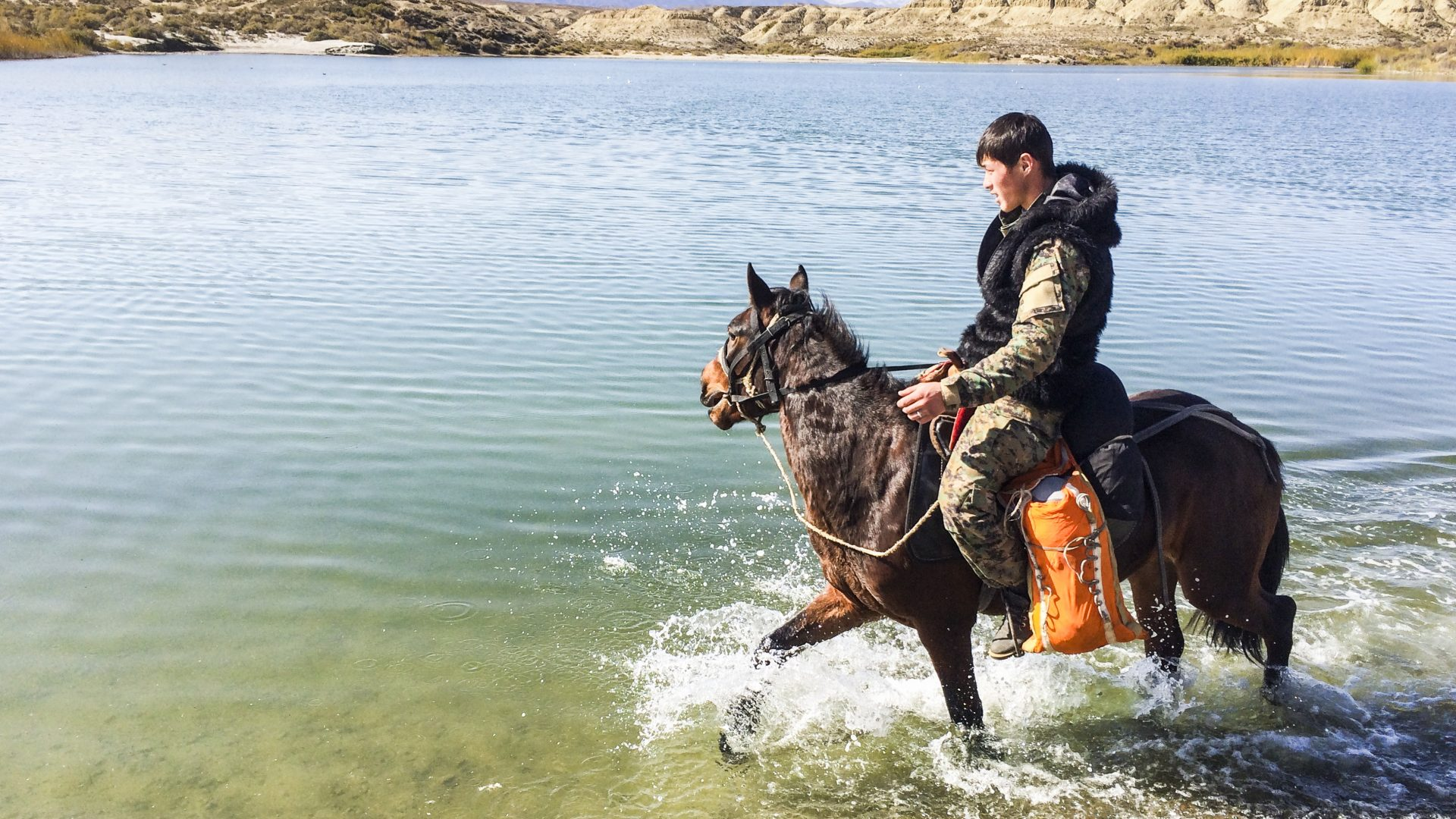 Man rides horse through water in Kyrgyzstan