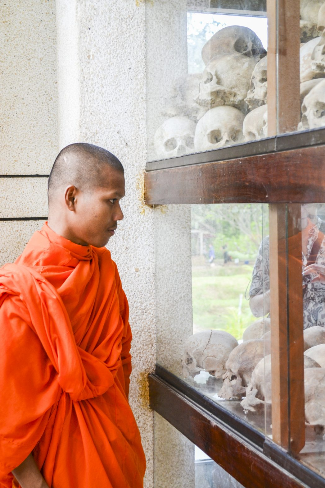 A young monk looks at the skulls and bones inside the memorial stupa at Choeung Ek outside Cambodia's capital Phnom Penh.