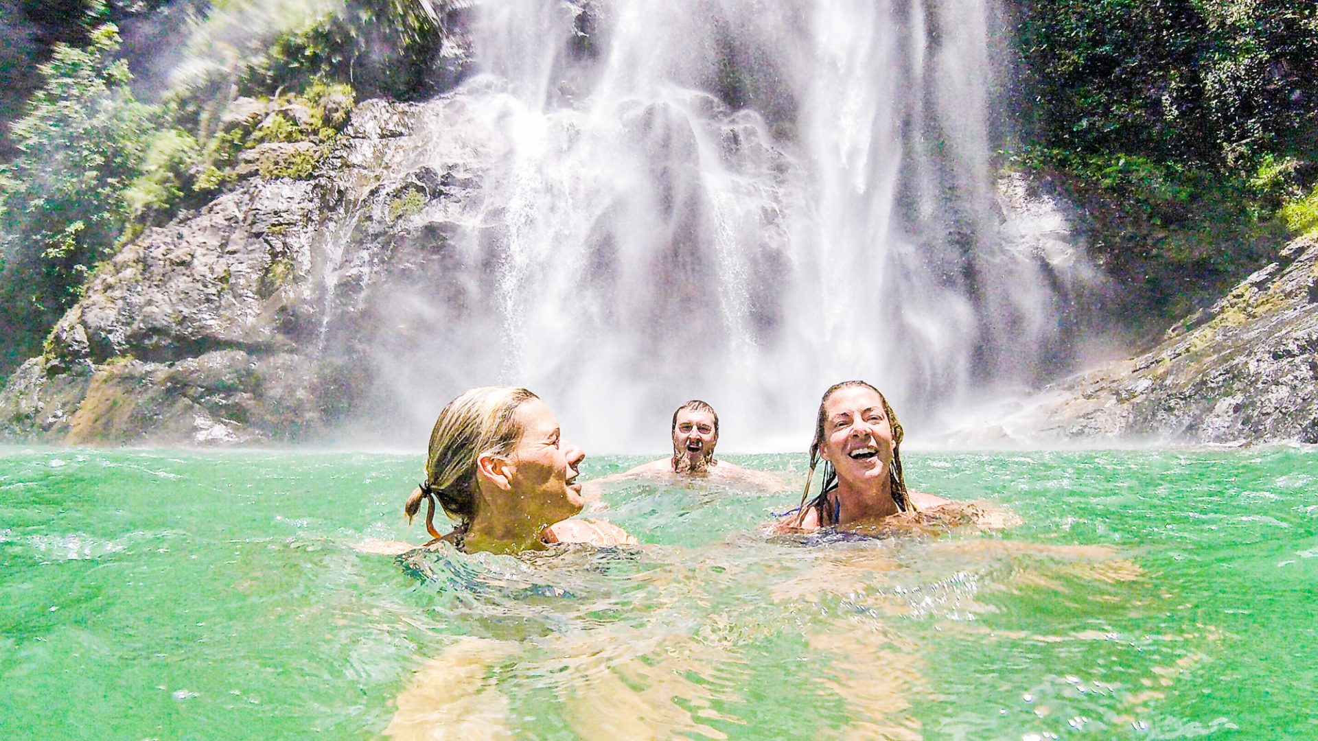 Three participants on an Adventure Academy trip swim in a turquoise natural pool.