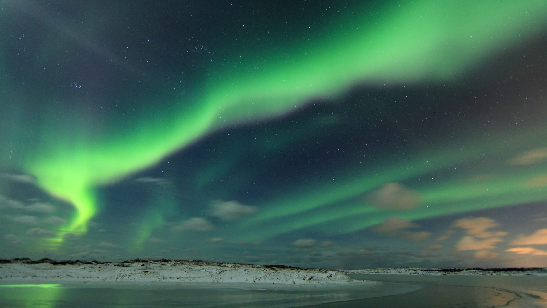 The Northern Lights over the Icelandic coastline.