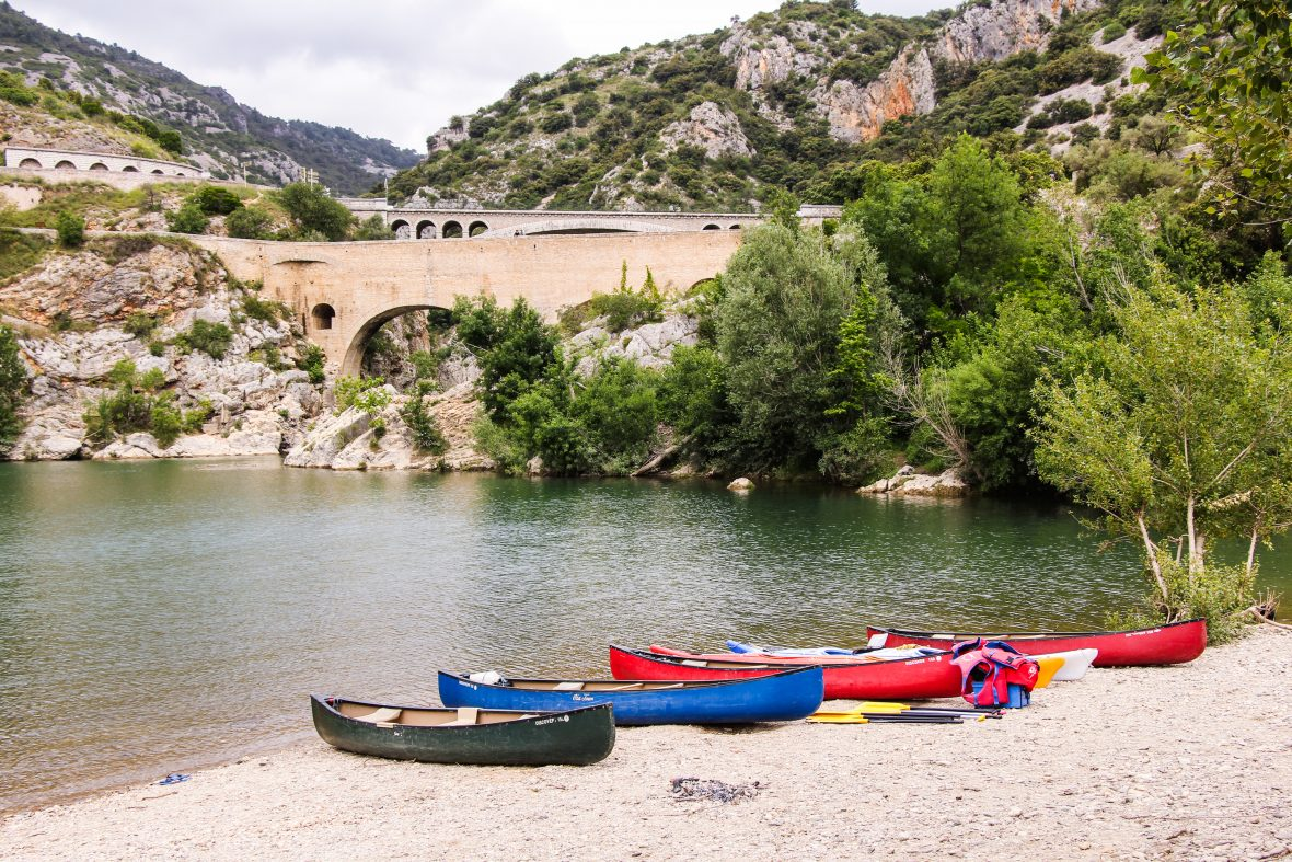 Brightly colored kayaks on the sand in the Vallée de l'Hérault: kayaking in France