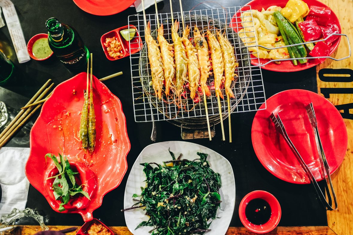 A dinner table displays a meal's worth of typical Vietnamese dishes.