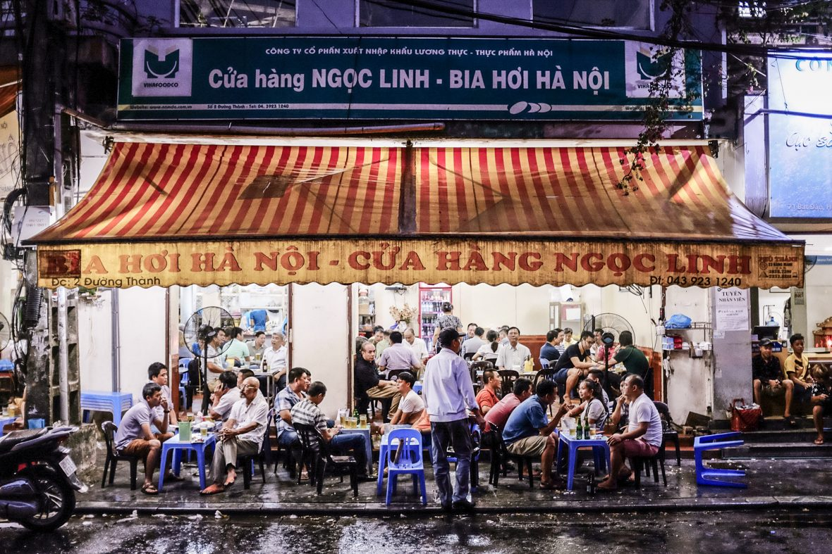 Crowds sit on plastic chairs to eat out the front of a typical Vietnamese eatery in Vietnam.