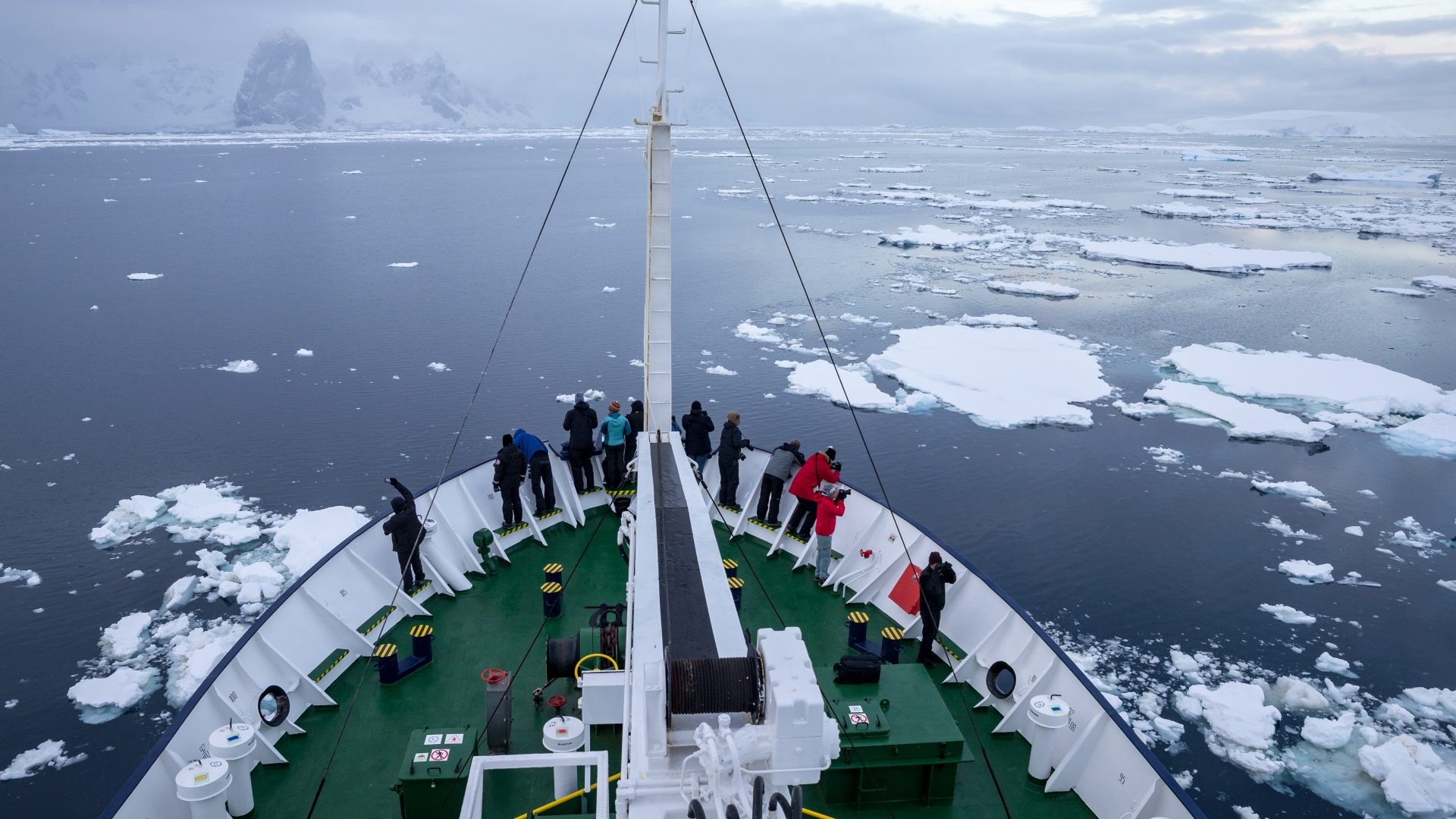 Passengers can be seen from above, looking out over the deck of their ship as it moves through the water in Antarctica.