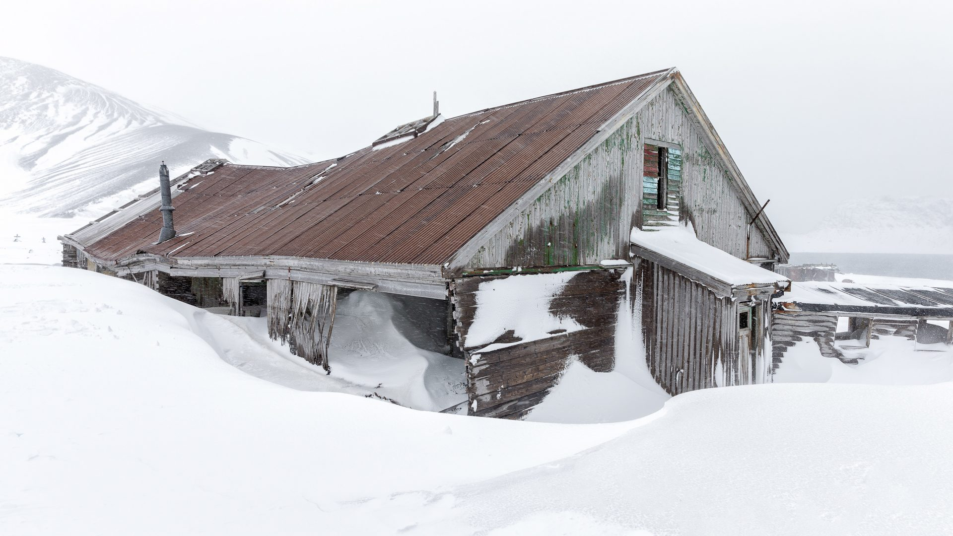 An abandoned building at an old whaling station is surrounded by snow.