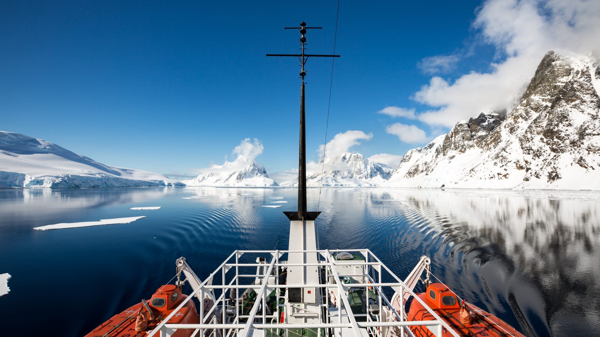 The ship passes through the calm water of Antartica, flanked by icebergs on all sides.