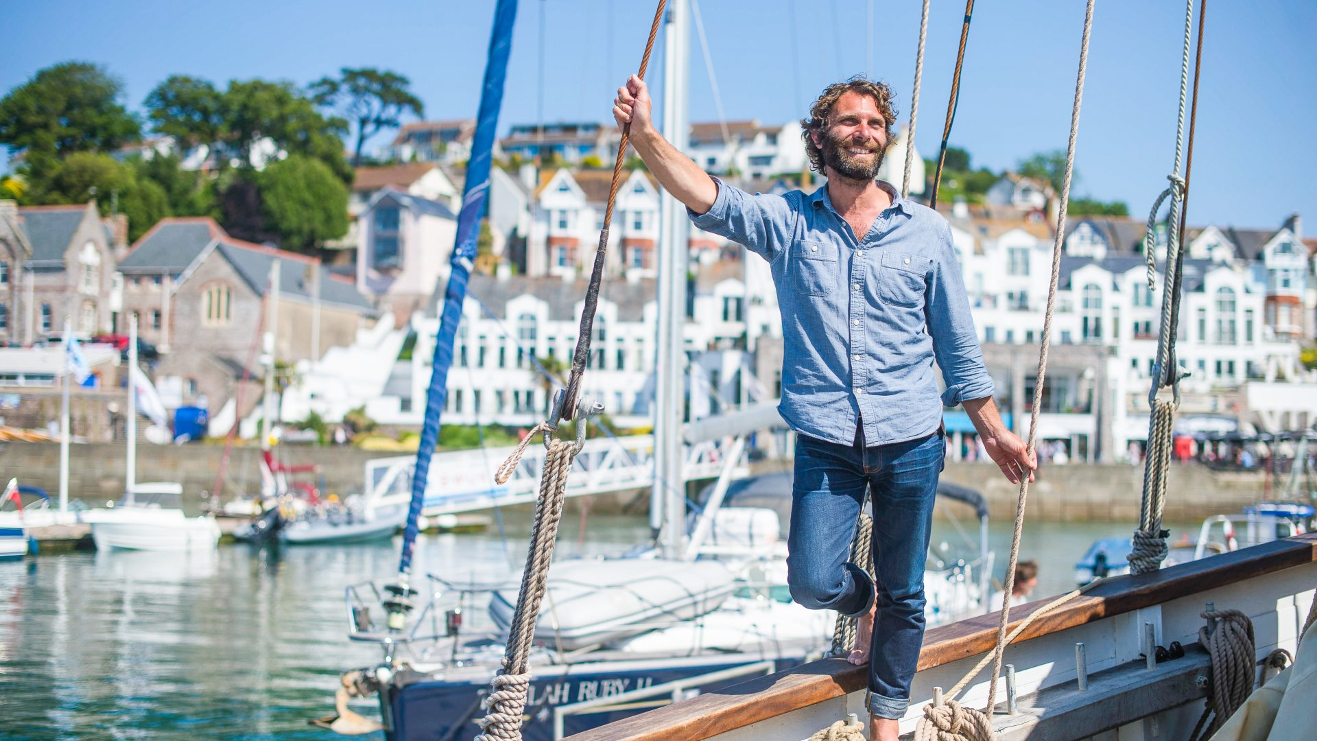 Travel writer James Stewart pictured on the Grayhound, a Cornish Lugger, in Brixham Marina, South Devon