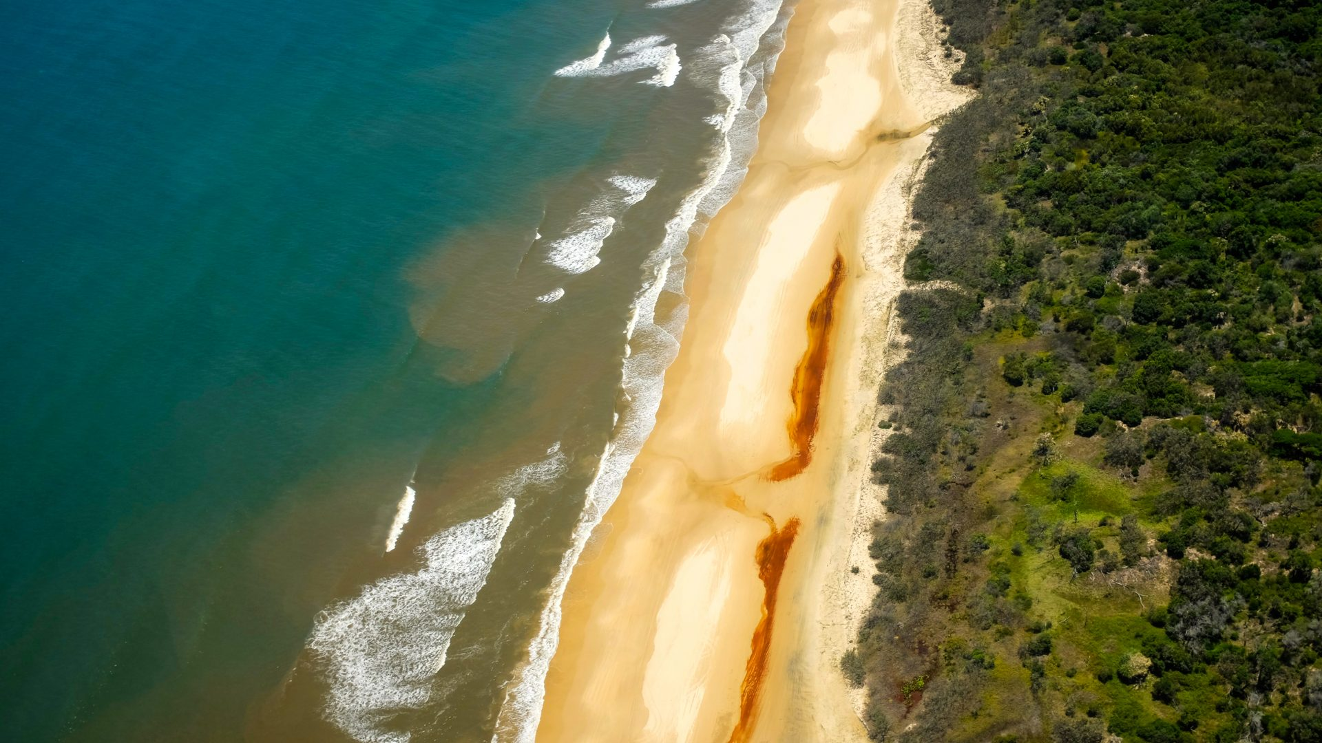 An aerial view over the green waters and yellow sands of a beach in Australia.