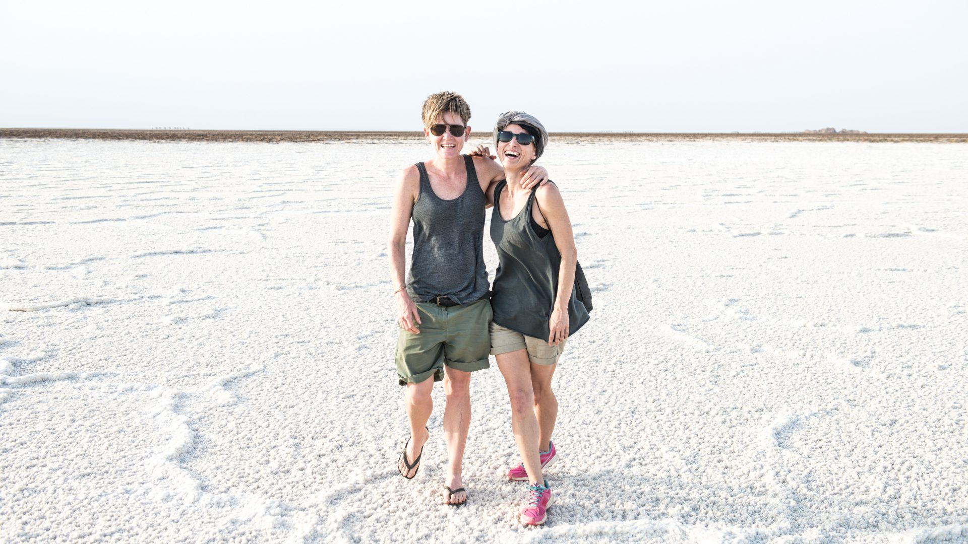 Two women can be seen standing in the white salt of the salt plains, located in the North East of Ethiopia.