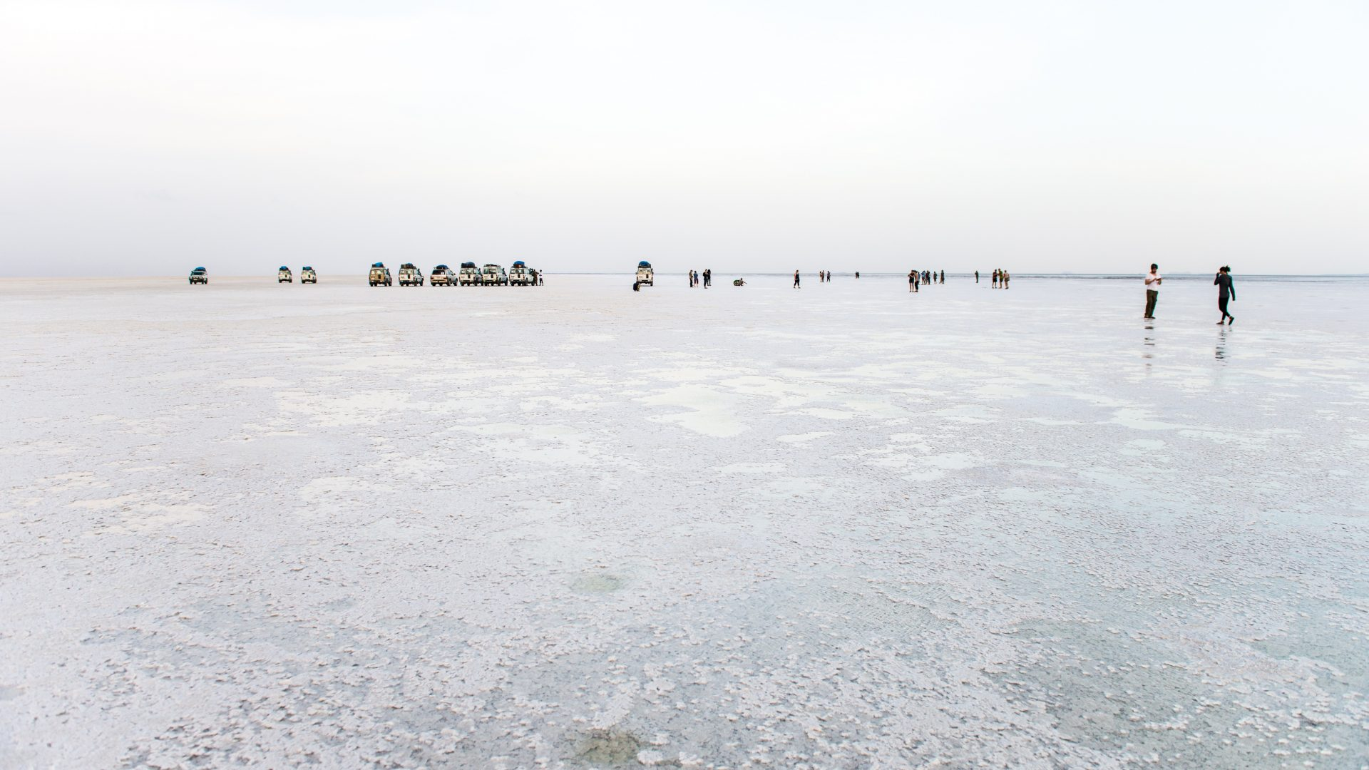 Appearing small in the distance, jeeps and tourists can be seen waiting in a row on the salt plains in the North East of Ethiopia.