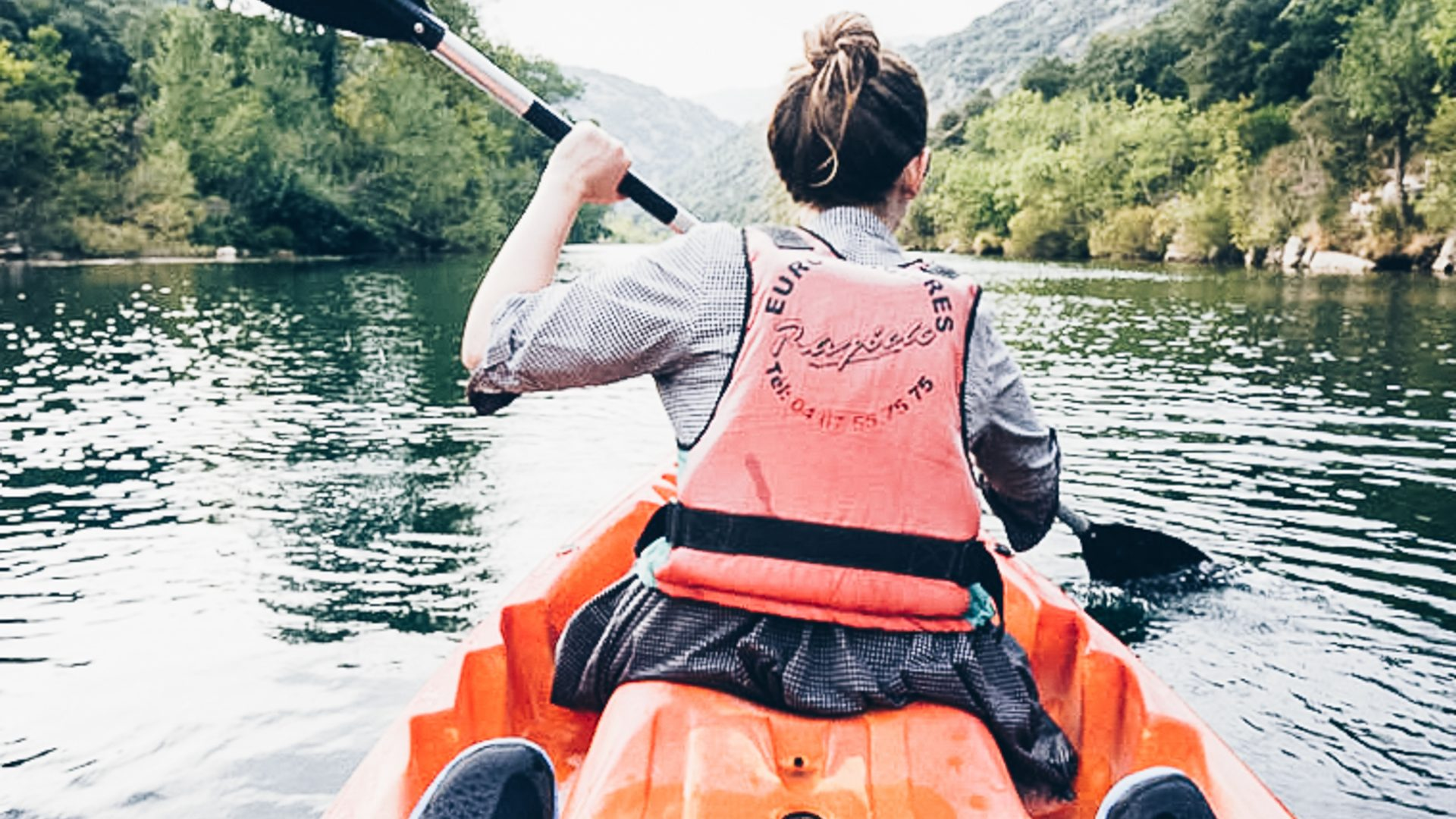 Rosie's back is visible as she kayaks down the river in Vallée de l'Hérault; kayaking in France