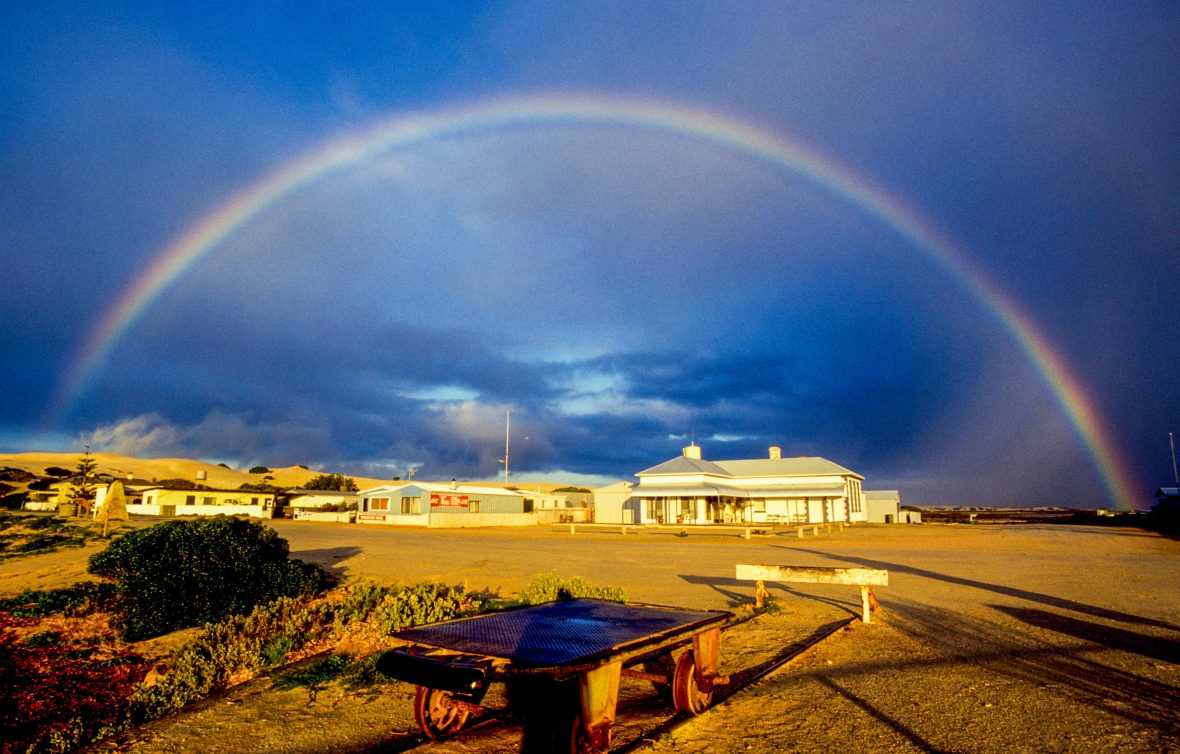 Hitchhiking Australia: a rainbow forms a perfect arc over a town in the outback.