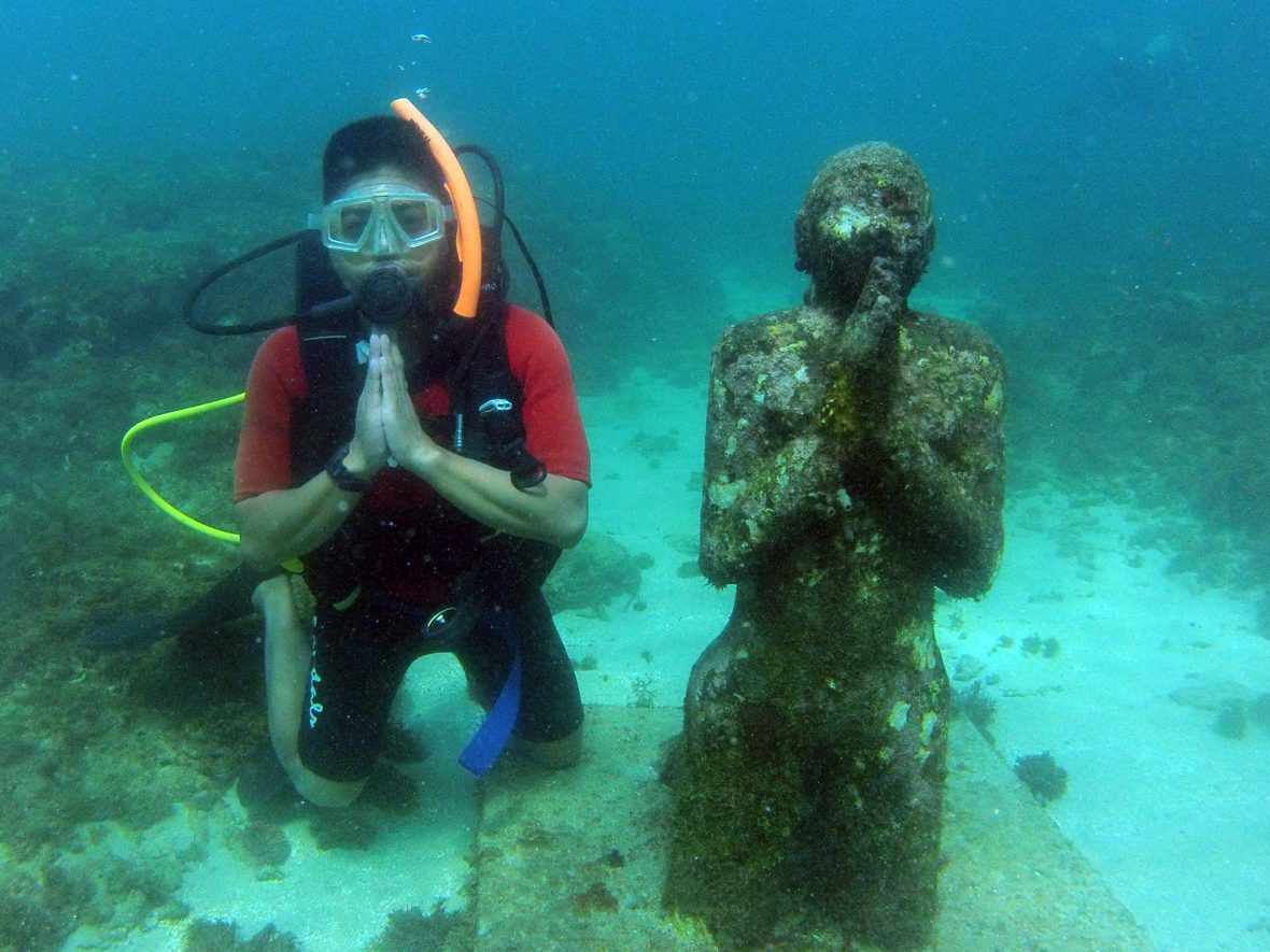 A snorkeler poses alongside one of the pieces in the underwater sculptural piece known as Vicissitudes by British artist Jason deCaires Taylor.