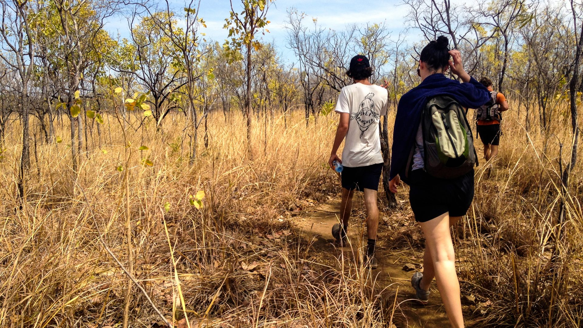 Travelers hike through the yellowing grasses of the Outback in Australia.