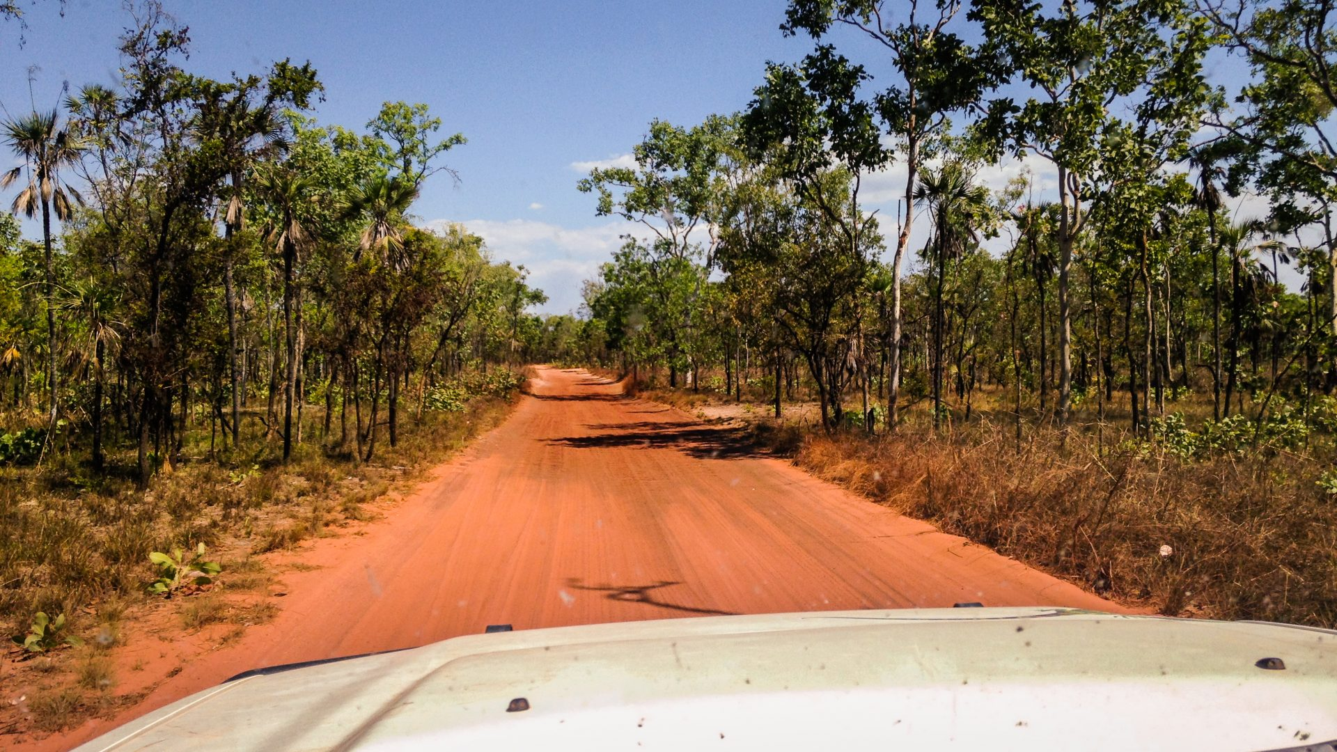 A jeep drives along a red road in the Australian Outback.