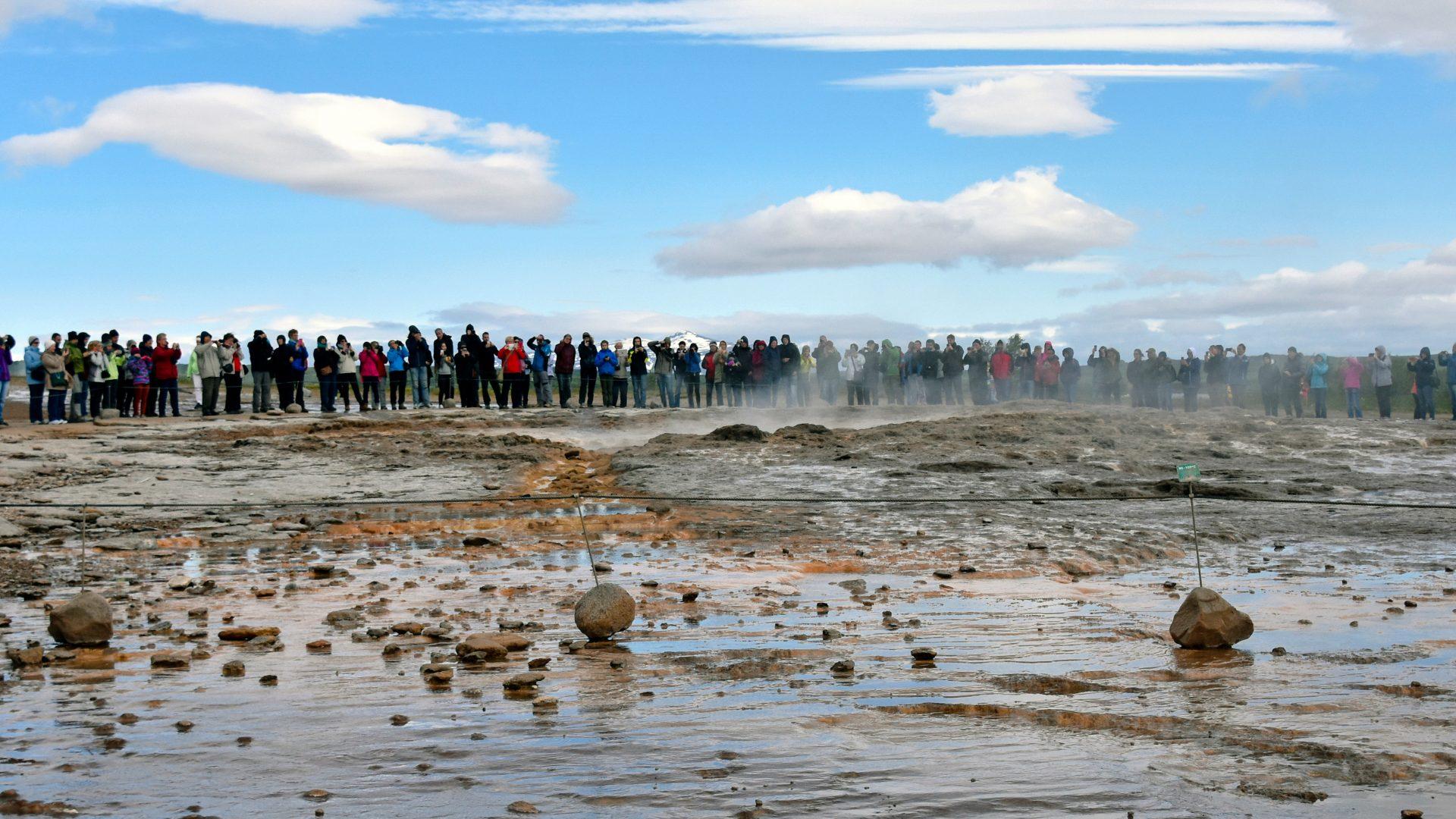 A crowd waiting waiting for the Strokkur Geyser eruption in Reykjavík, Iceland