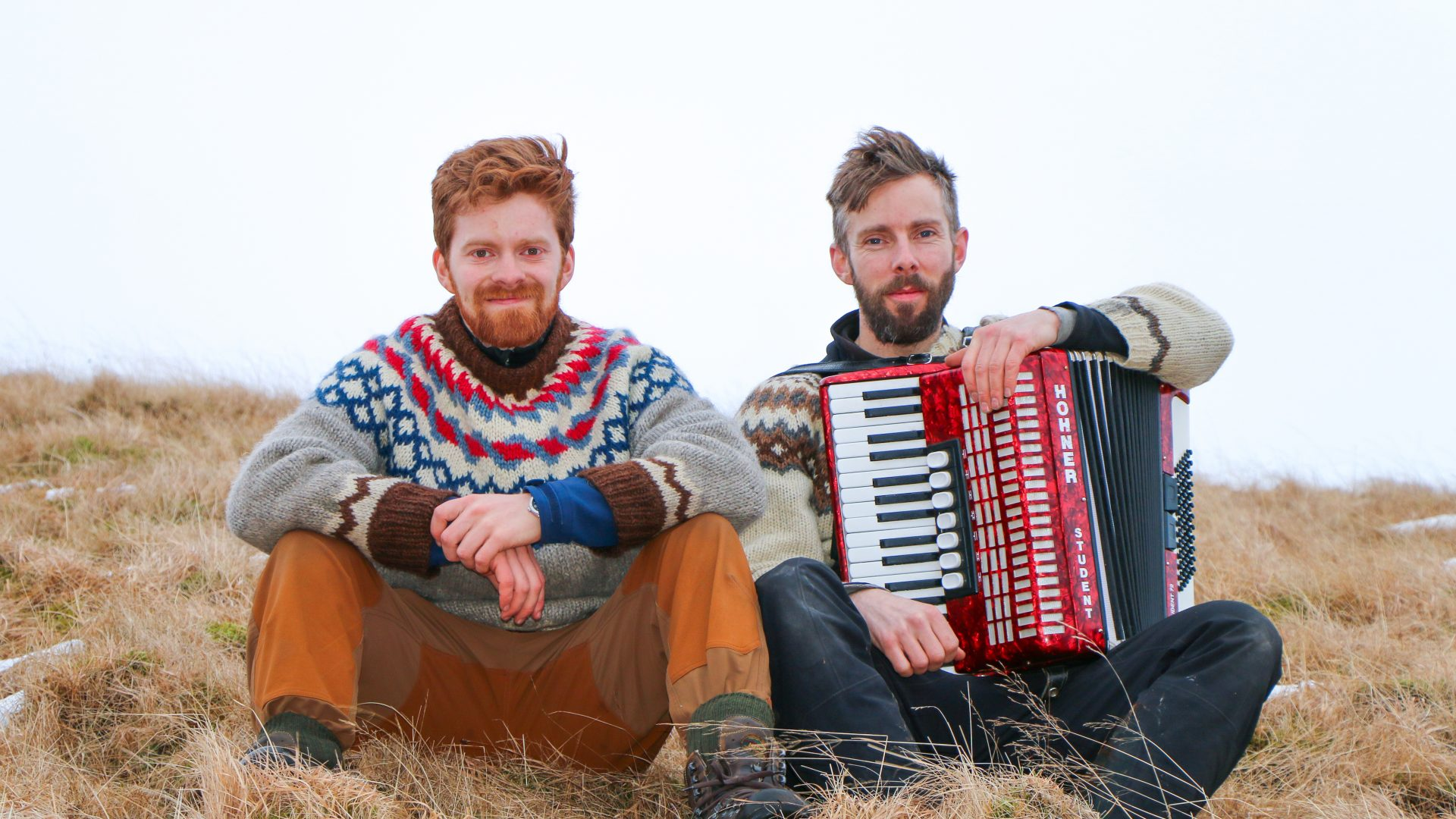 Men sit with an accordion on a hill in Iceland