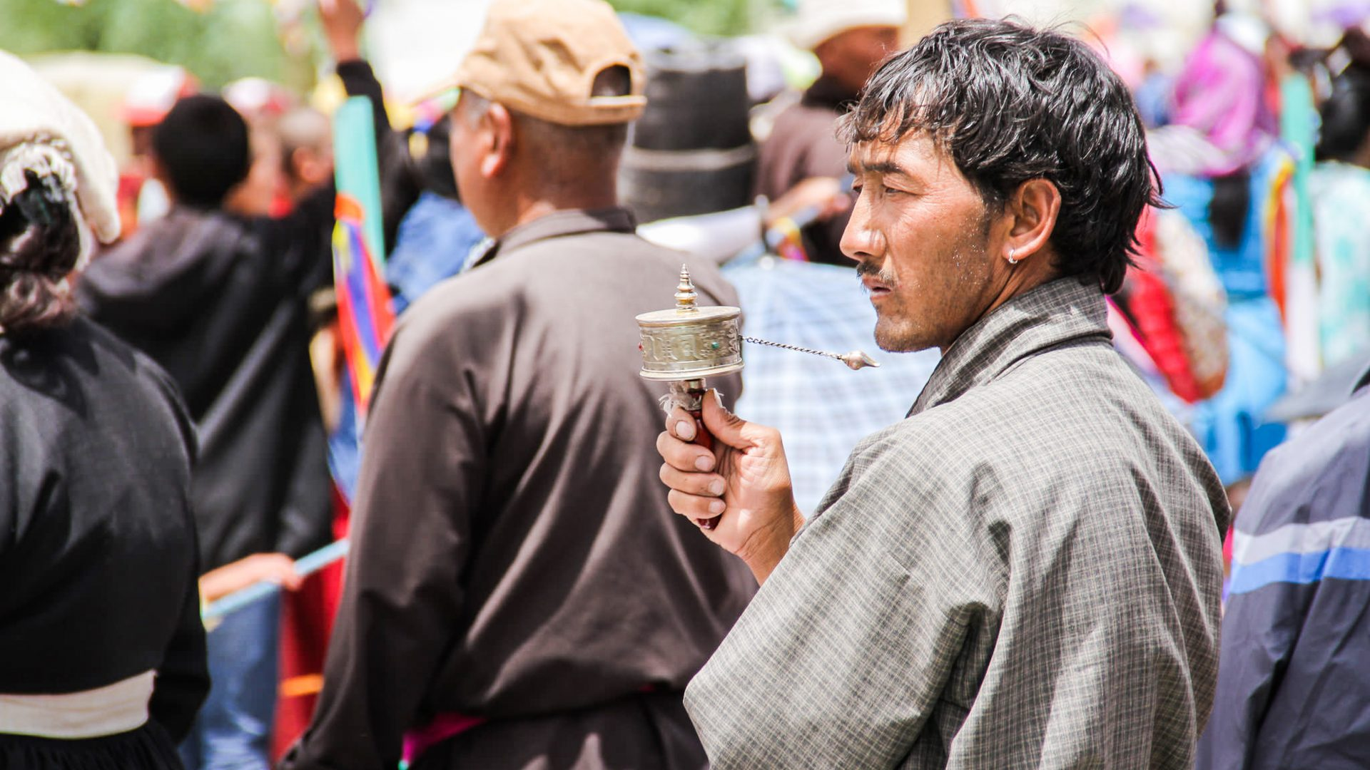 A man spins his personal prayer wheel at the Buddhist festival in Ladakh in the Himalayas