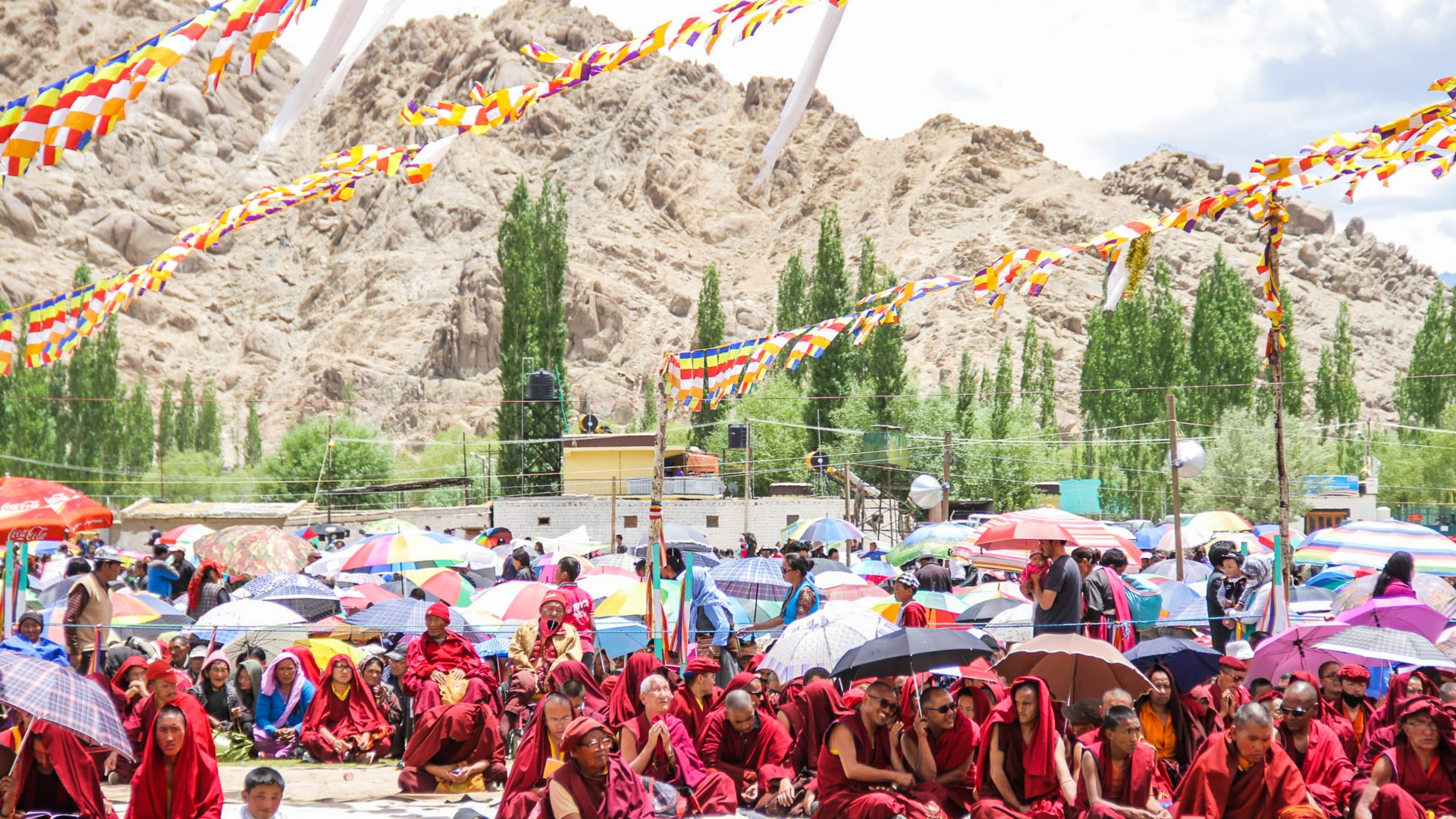 Monks in their traditional red robes can be seen sitting on the ground at the Buddhist festival in Ladakh in the Himalayas
