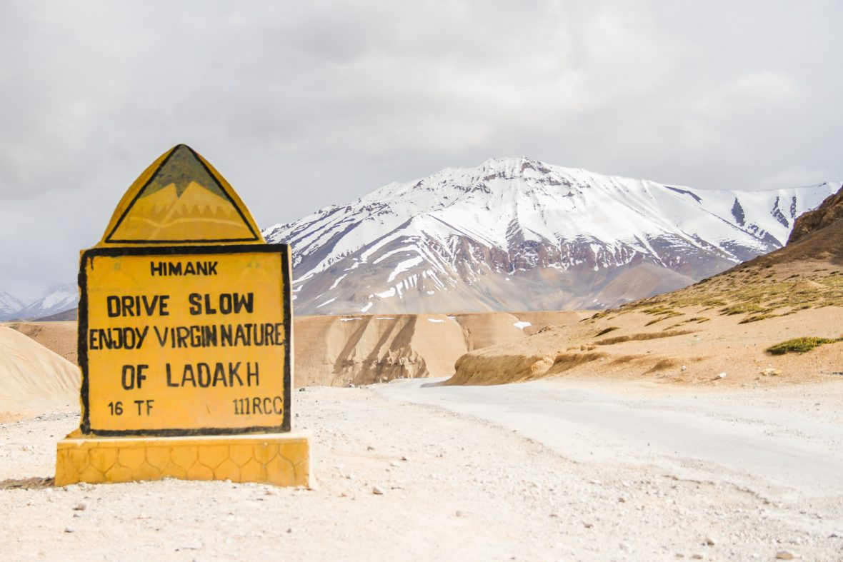 A road sign on the Manali to Leh Highway encourages drivers to drive slowly in the Himalayas.