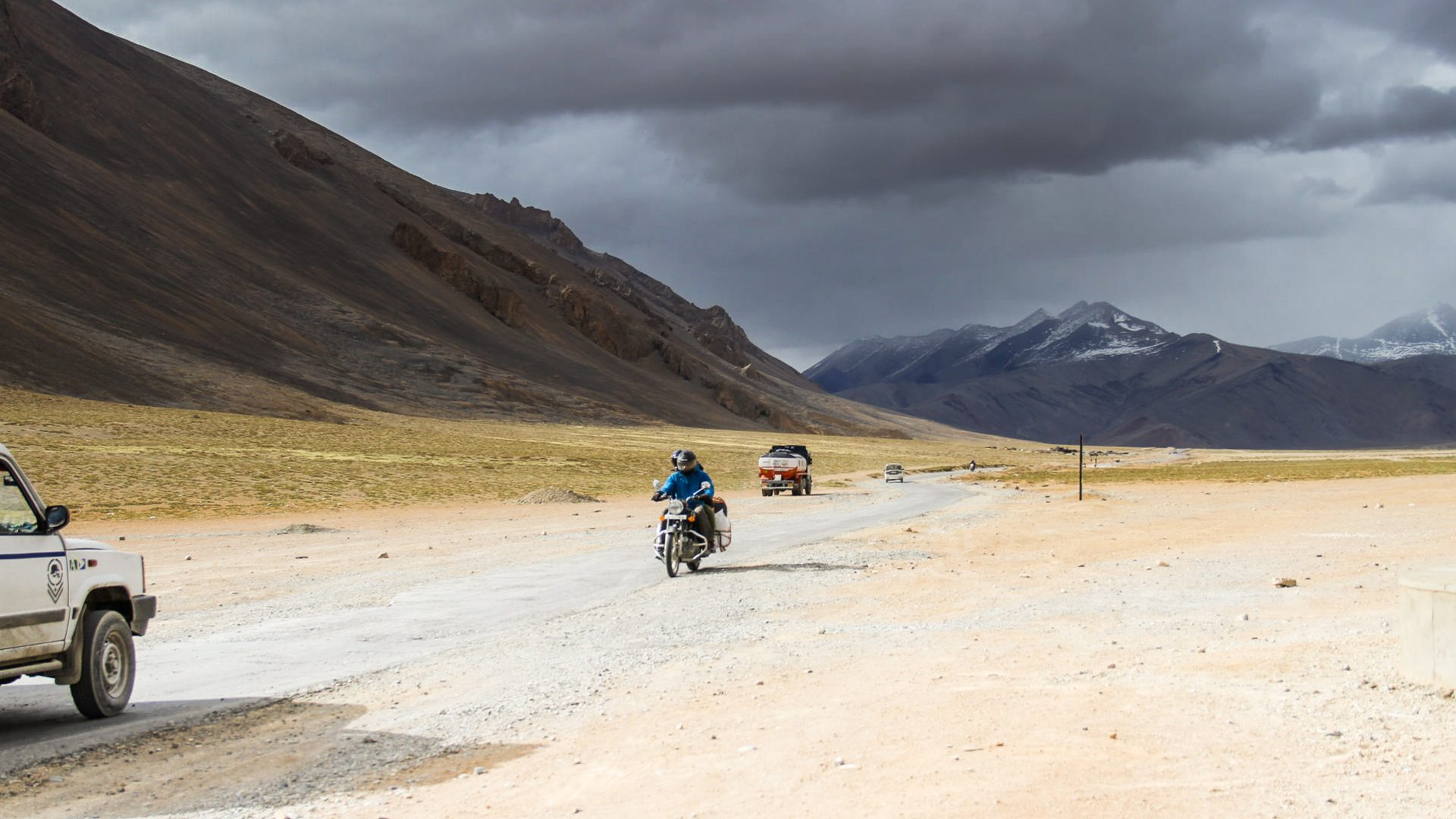 Trucks and motorcycles trail one another on the Manali to Leh Highway.