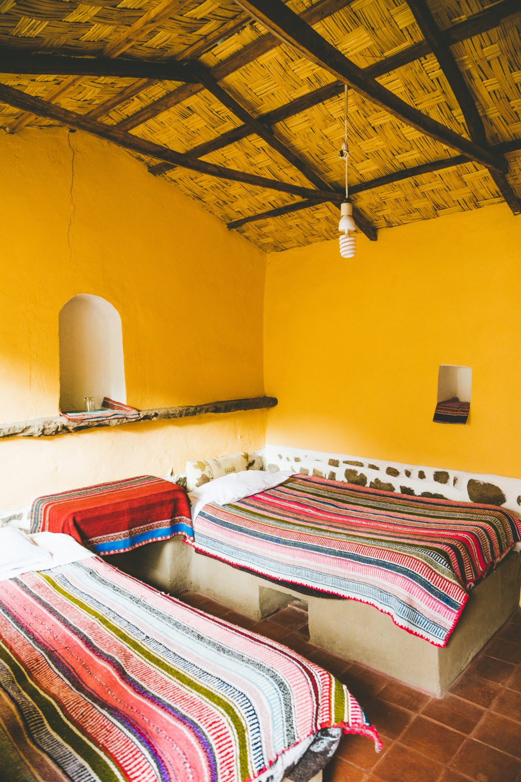 Interior of the homestay with beds covered in traditional colorful blankets and the walls a warm shade of yellow.
