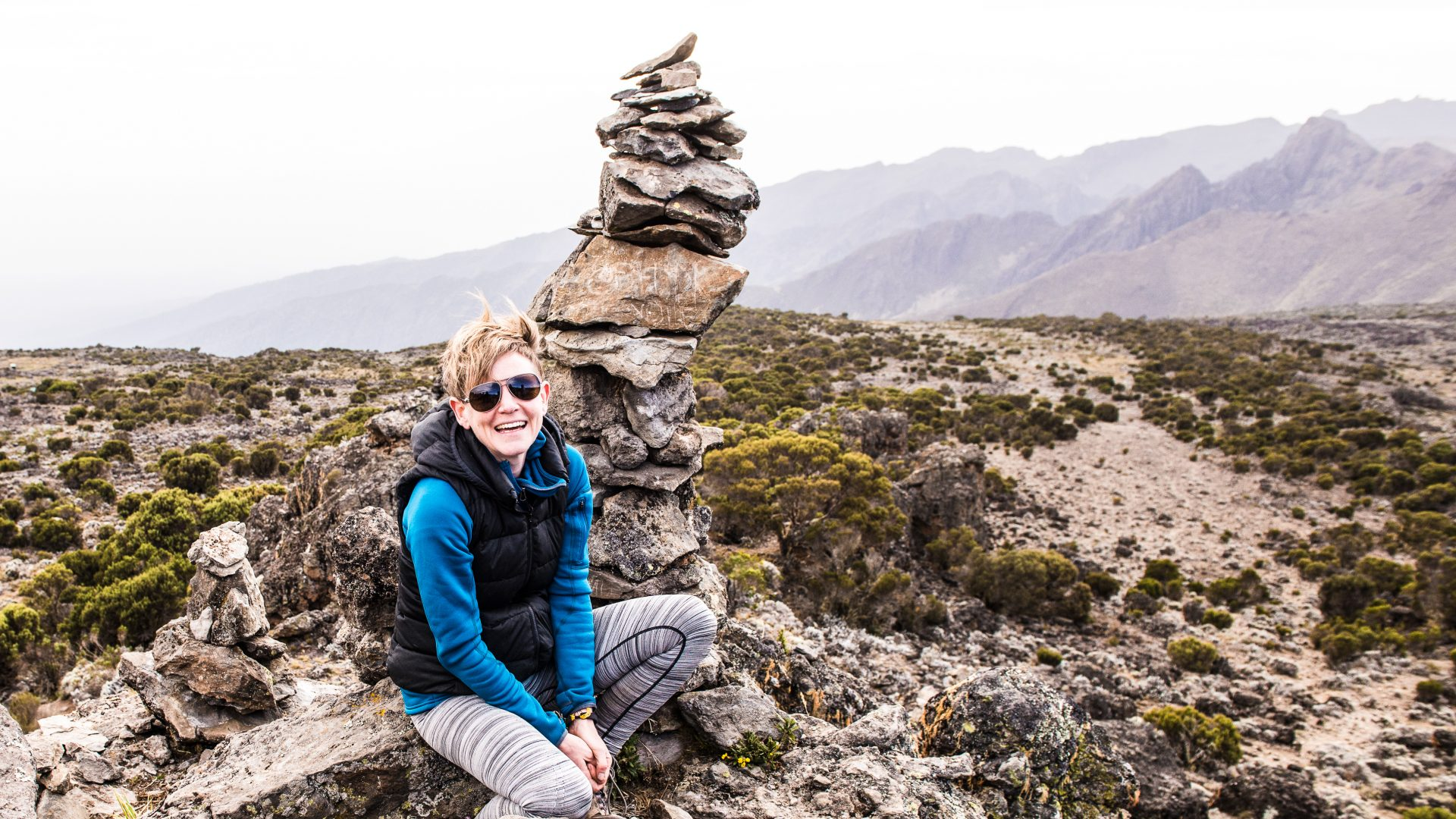 Contributor profile photo of Nicola Bailey. Sitting at a viewing spot during the hike to Mount Kilimanjaro