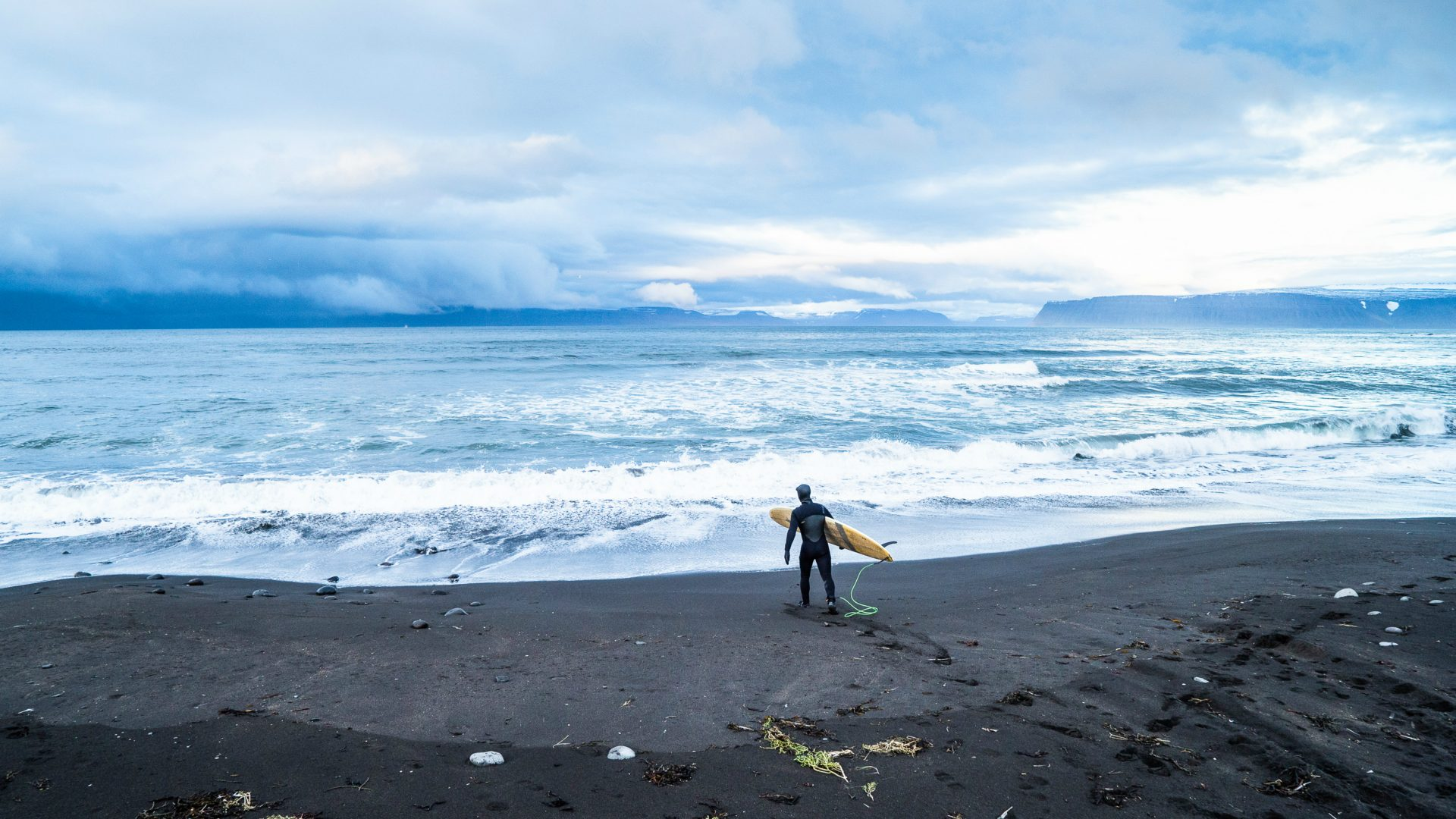 A surfer on the black sand beach in Bolungarvik, Iceland.