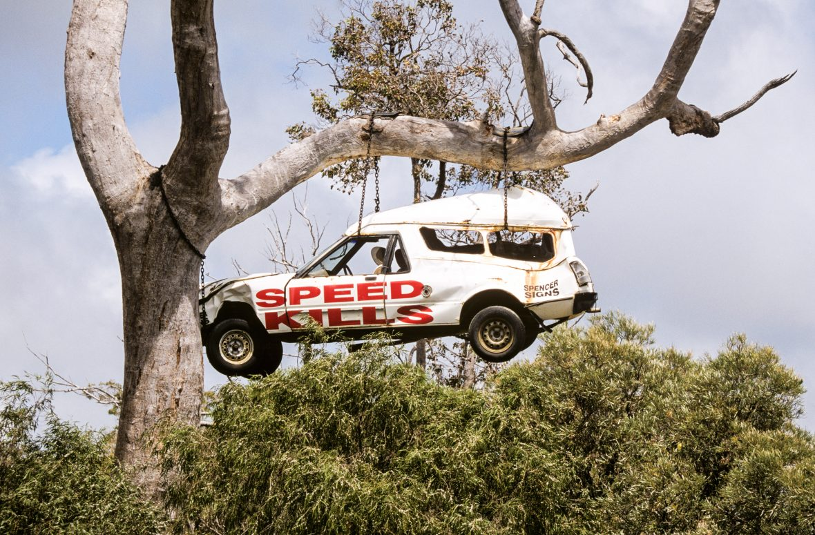 A smashed up car hanging from a tree in outback Australia warns drivers that speed kills.