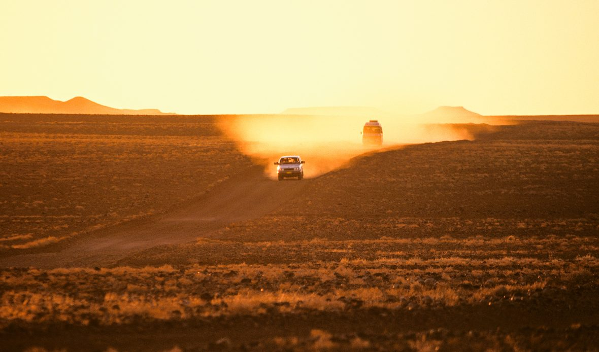 Hitchhiking Australi: A car leaves a trail of yellow dust at dusk in the outback.