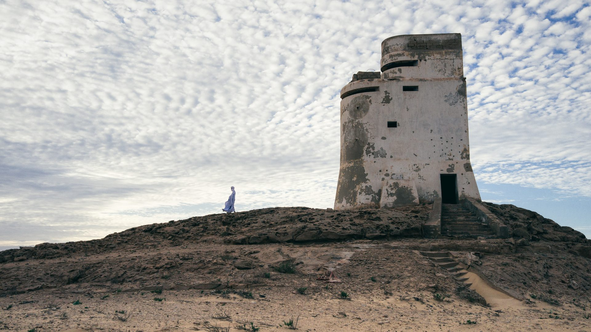 A Mauritanian man emerges from one of the abandoned war turrets that were used to defend the coastline from attack.