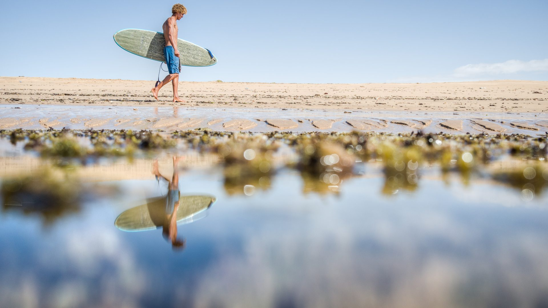 A surfers reflection in the shallow waters at low tide after a surf session around the giant shipwrecks.