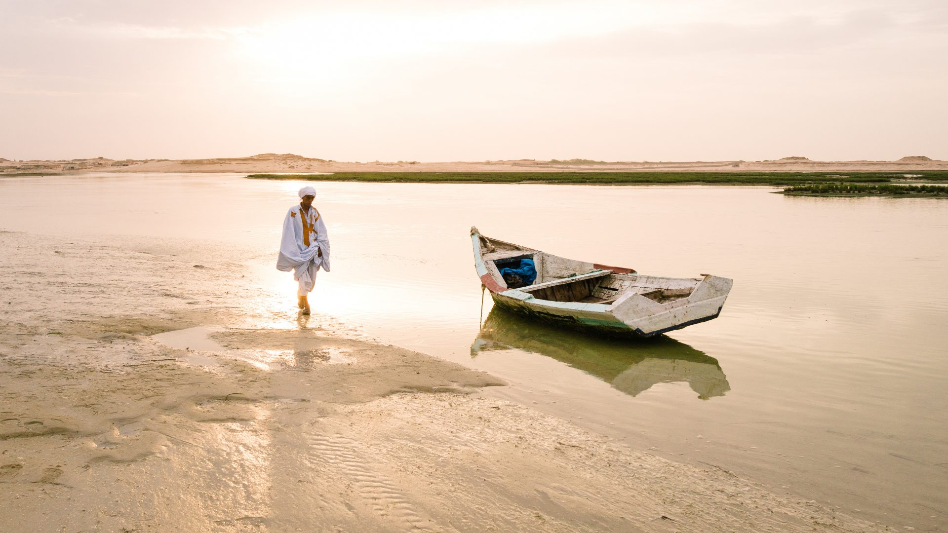 An Mauritania man walks near his boat at low tide just outside the town of Nouadhibou. The sandstorms coming off the Sahara desert leave the sky a surreal orange color.