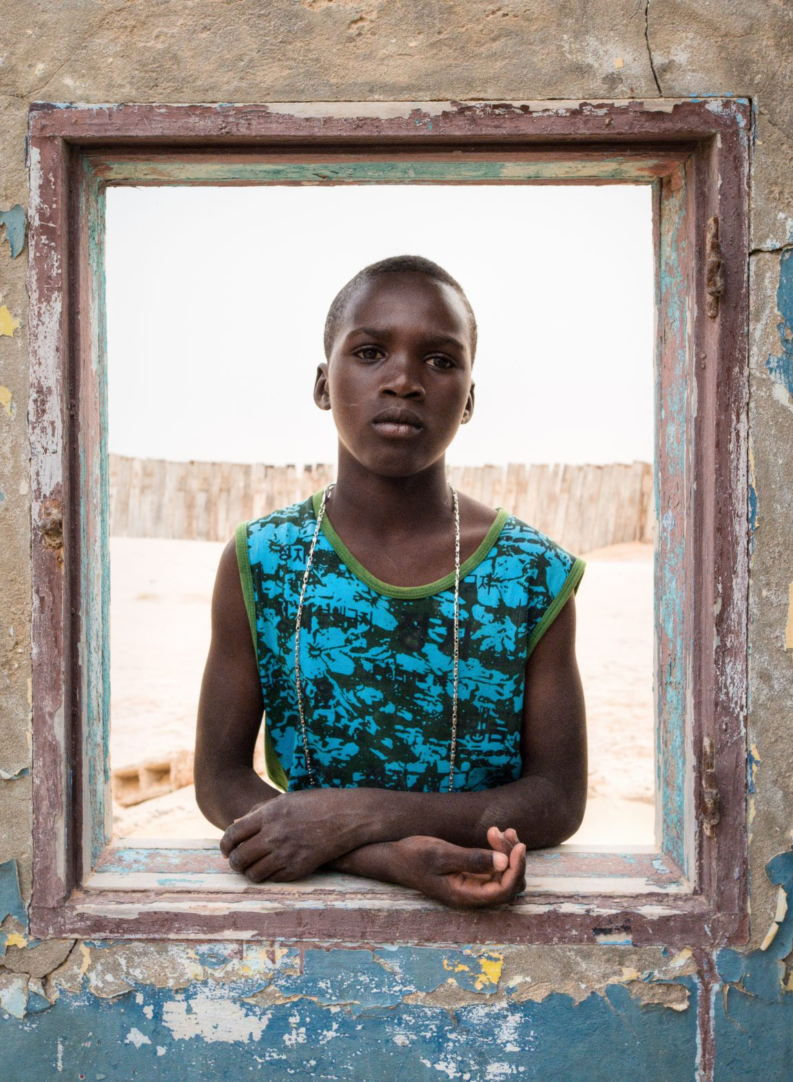 A young Mauritanian girl poses for a photo in the window of the many old buildings in Nouadhibou.