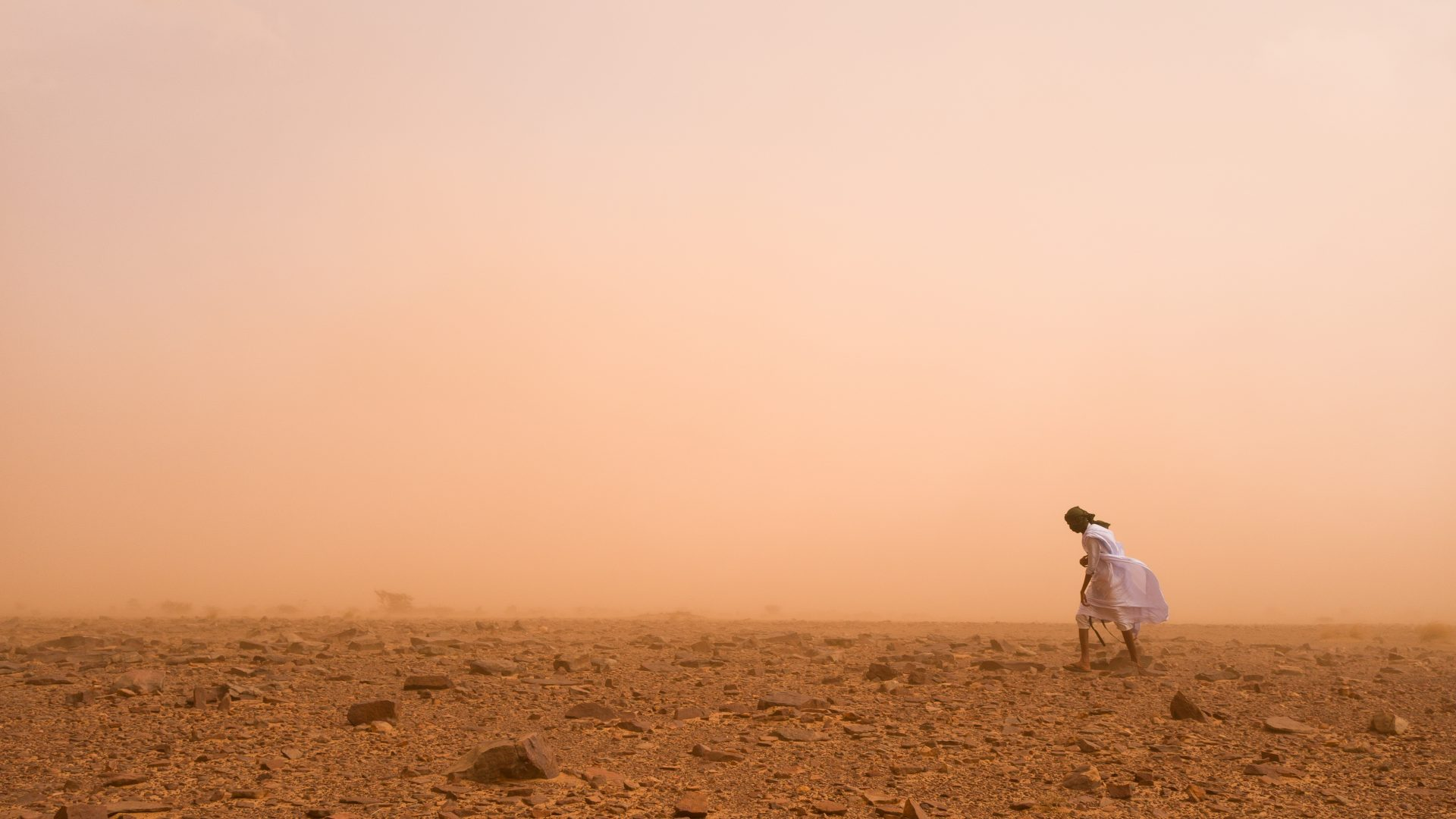 A Mauritanian man trying to walk through the strong winds of a desert sandstorm.