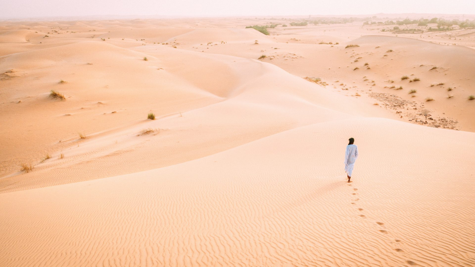 A local Mauritanian man walks into seemingly endless dunes of the Sahara desert.