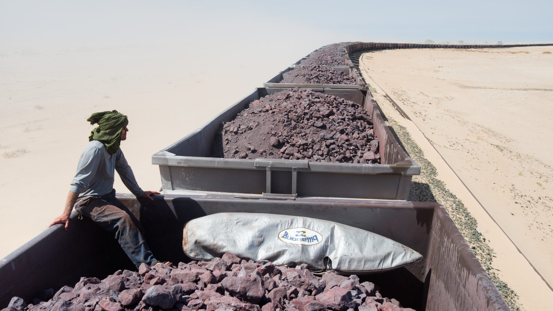 A man can be seen surveying the desert while sitting onboard the train, on top of piles of iron ore, during the long journey through the Sahara desert.