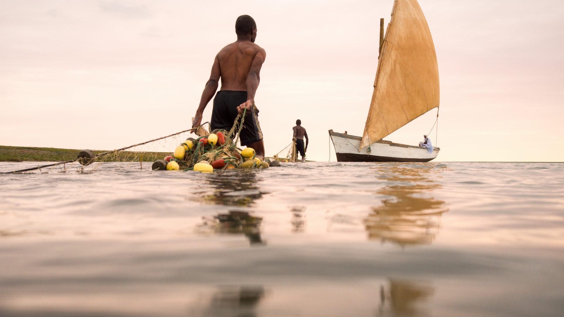 Imragruen fishermen drag their nets back to their traditional fishing boat.