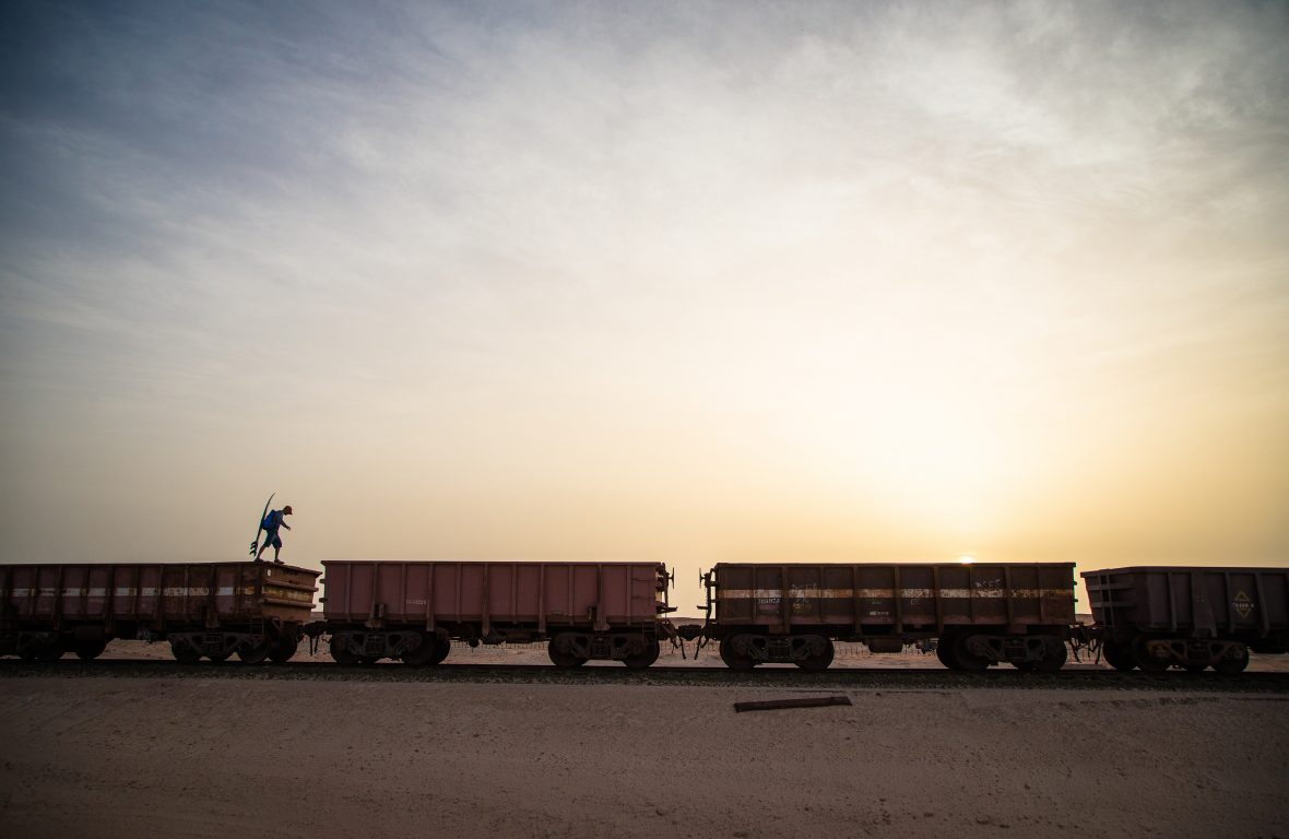 A traveler armed with his surfboard jumps from one train car to another during a beautiful sunset over the Sahara desert.