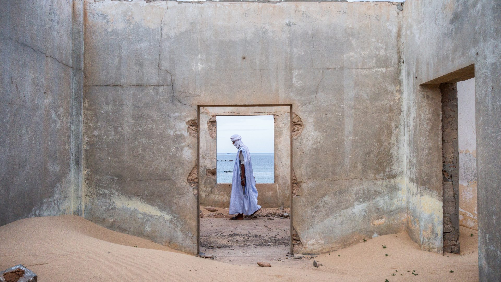 A Mauritanian man walks through one of the many abandoned buildings in the city of Nouadhibou