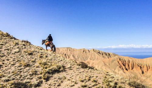 A man on horseback climbs steep hills of Kyrgyzstan.