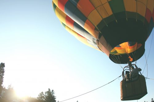 A hot air balloon takes off in the sunlight